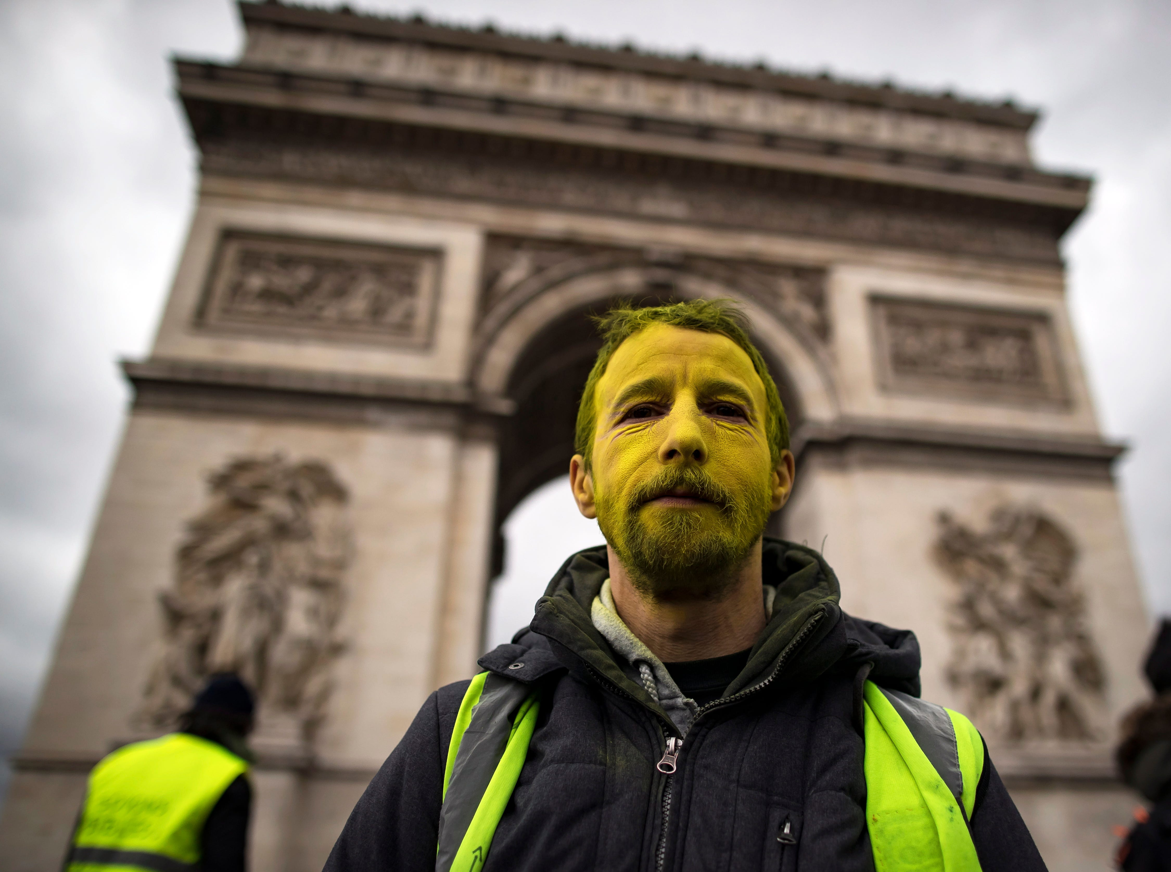 A protester from the 'Gilets Jaunes' (Yellow Vests) movement walks down the Champs Elysees avenue near the Arc de Tiomphe during the 'Act XVII' demonstration in Paris, France on March 9, 2019.