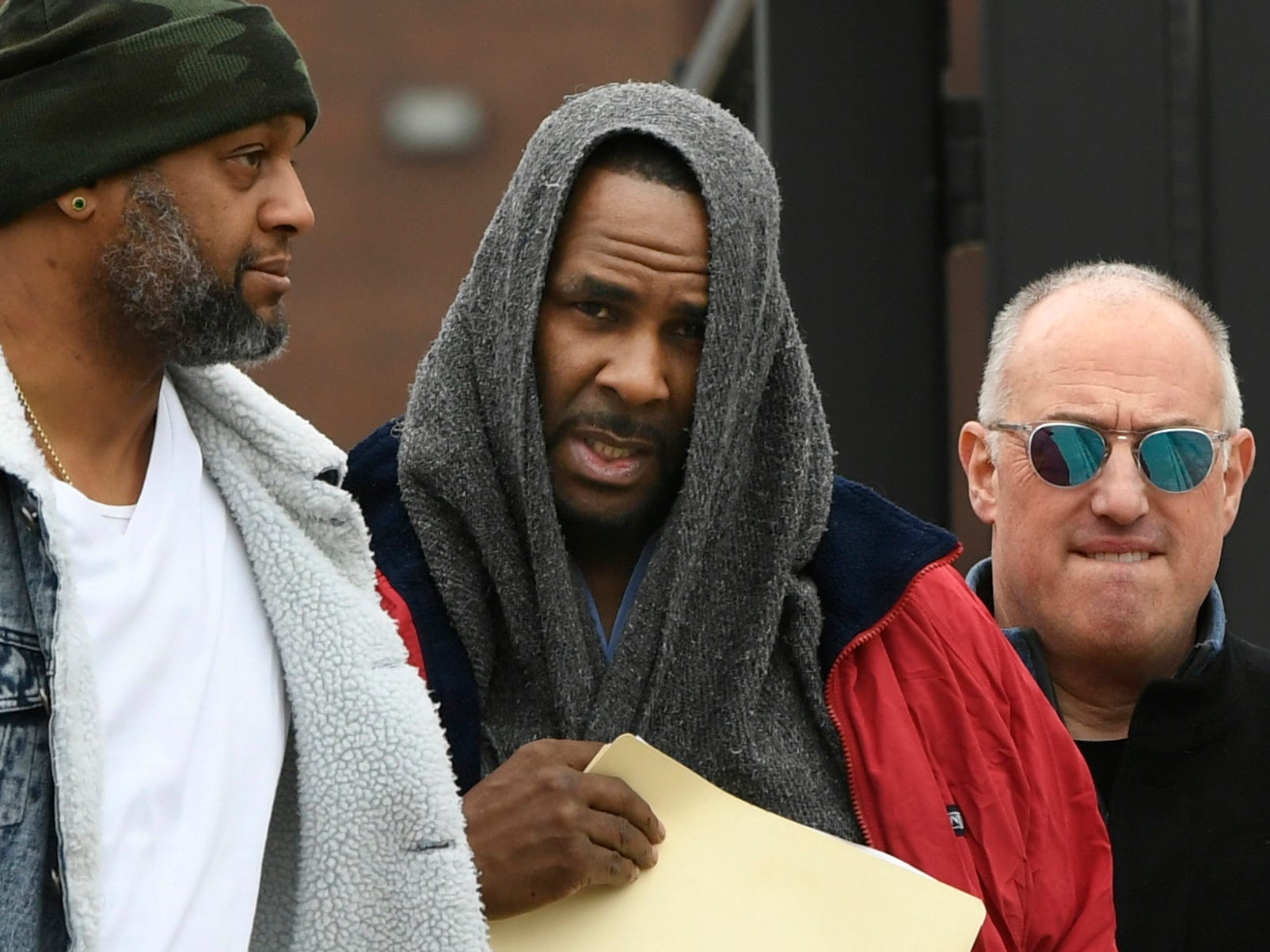 Singer R. Kelly center, walks with his attorney Steve Greenberg right, and an unidentified man left, who gave him a ride after being released from Cook County Jail, March 9, 2019, in Chicago.