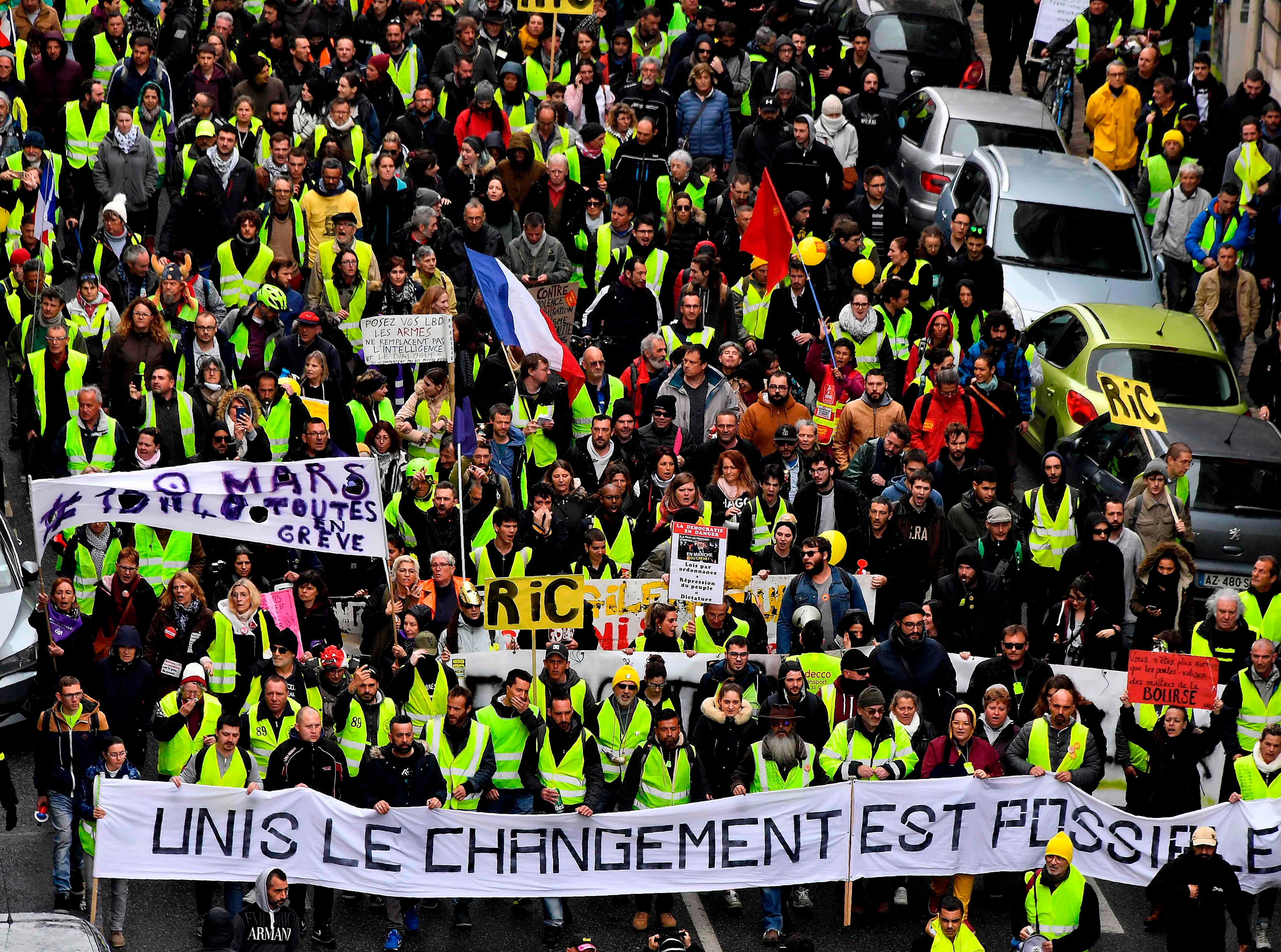 "Protesters hold a banner reading ""United, the change is possible"" as they take part in an anti-government demonstration called by the ""Yellow Vests"" (Gilets jaunes) movement in Bordeaux, southwestern France, on March 9, 2019."
