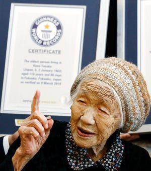 Kane Tanaka, a 116-year-old Japanese woman, gestures after receiving a Guinness World Records certificate, back, at a nursing home where she lives in Fukuoka, southwestern Japan, on March 9, 2019.