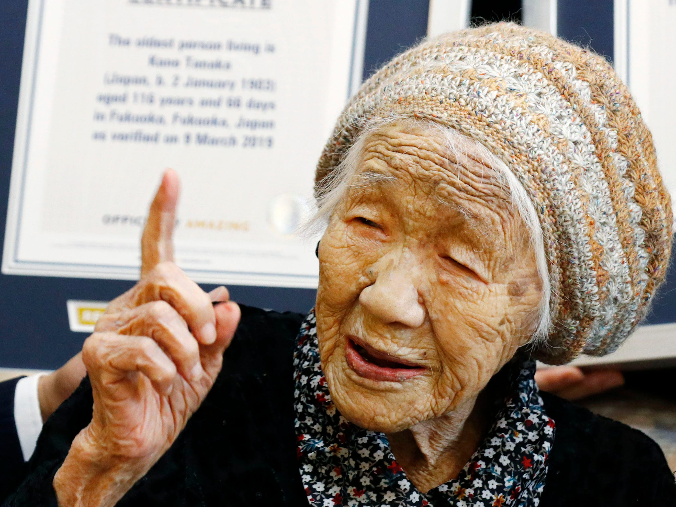 Kane Tanaka, a 116-year-old Japanese woman, gestures after receiving a Guinness World Records certificate, back, at a nursing home where she lives in Fukuoka, Japan on Saturday, March 9, 2019.