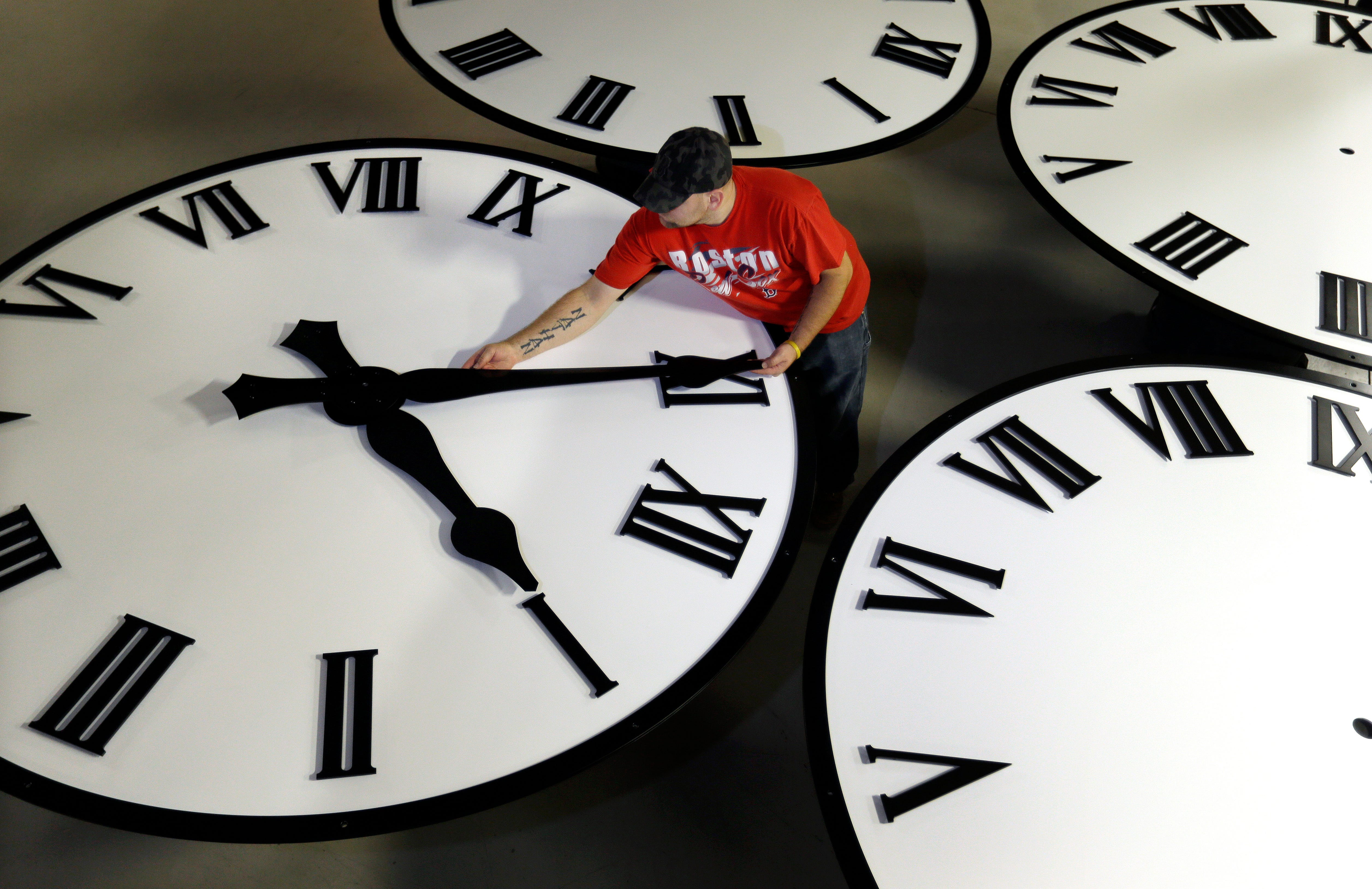 Dan LaMoore sizes hands for an 8-foot diameter silhouette clock at Electric Time Co., in Medfield, Massachusetts.