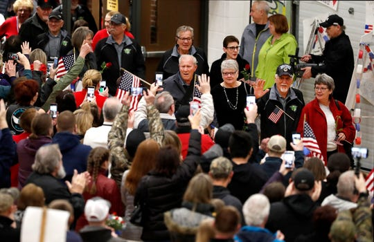 Vietnam veterans are greeted by a crowd of people during the Old Glory Honor Flight-Return to Nam welcome home Saturday, March 9, 2019, at Menasha High School in Menasha, Wis. Veterans were greeted by friends, family, the Menasha High School band, and the 484th Army Band.