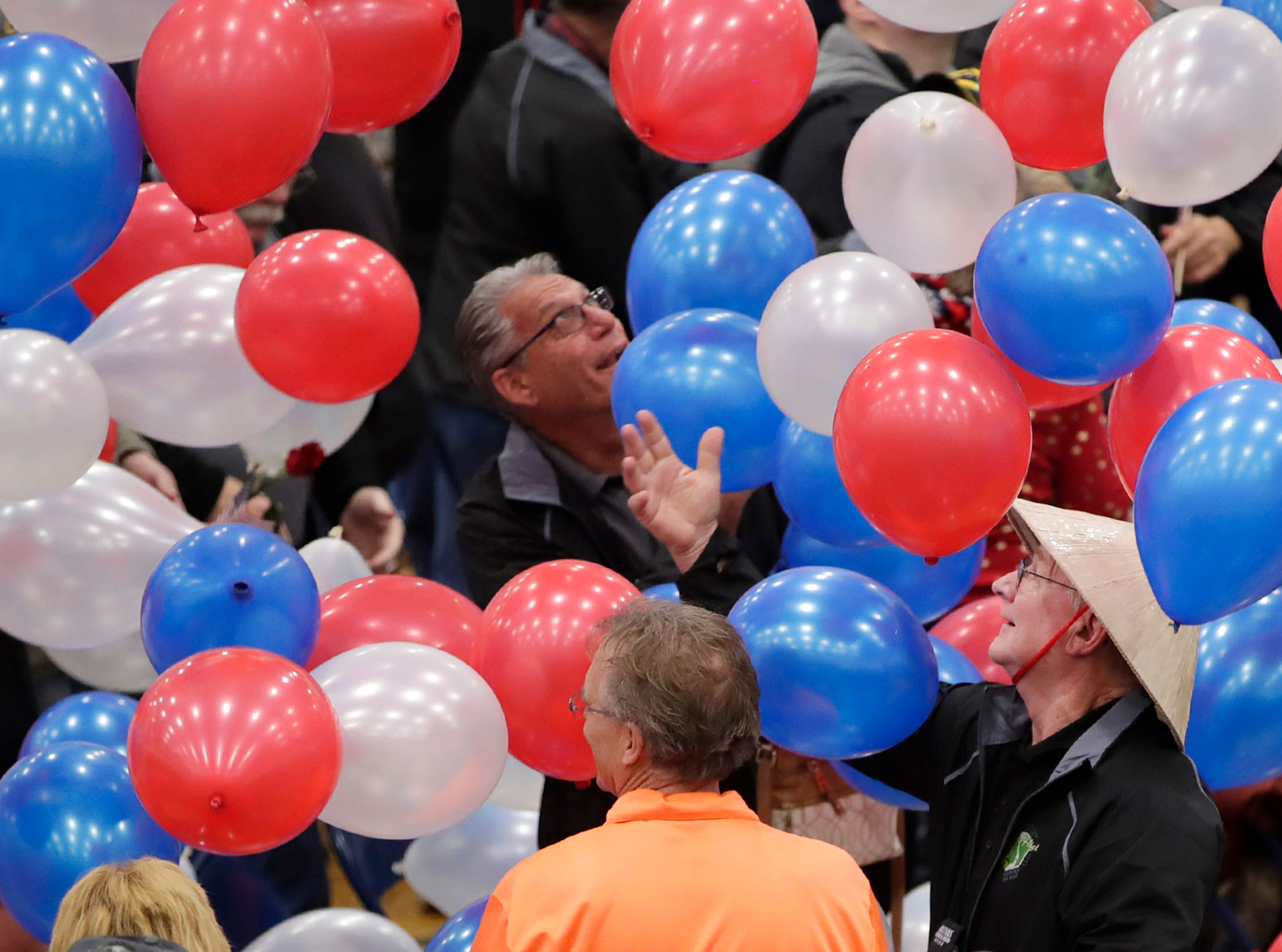 Dennis Helke, of Manitowac, reaches for falling balloons at the end of the welcome home ceremony during the Old Glory Honor Flight-Return to Nam welcome home Saturday, March 9, 2019, at Menasha High School in Menasha, Wis. Veterans were greeted by friends, family, the Menasha High School band, and the 484th Army Band.Danny Damiani/USA TODAY NETWORK-Wisconsin