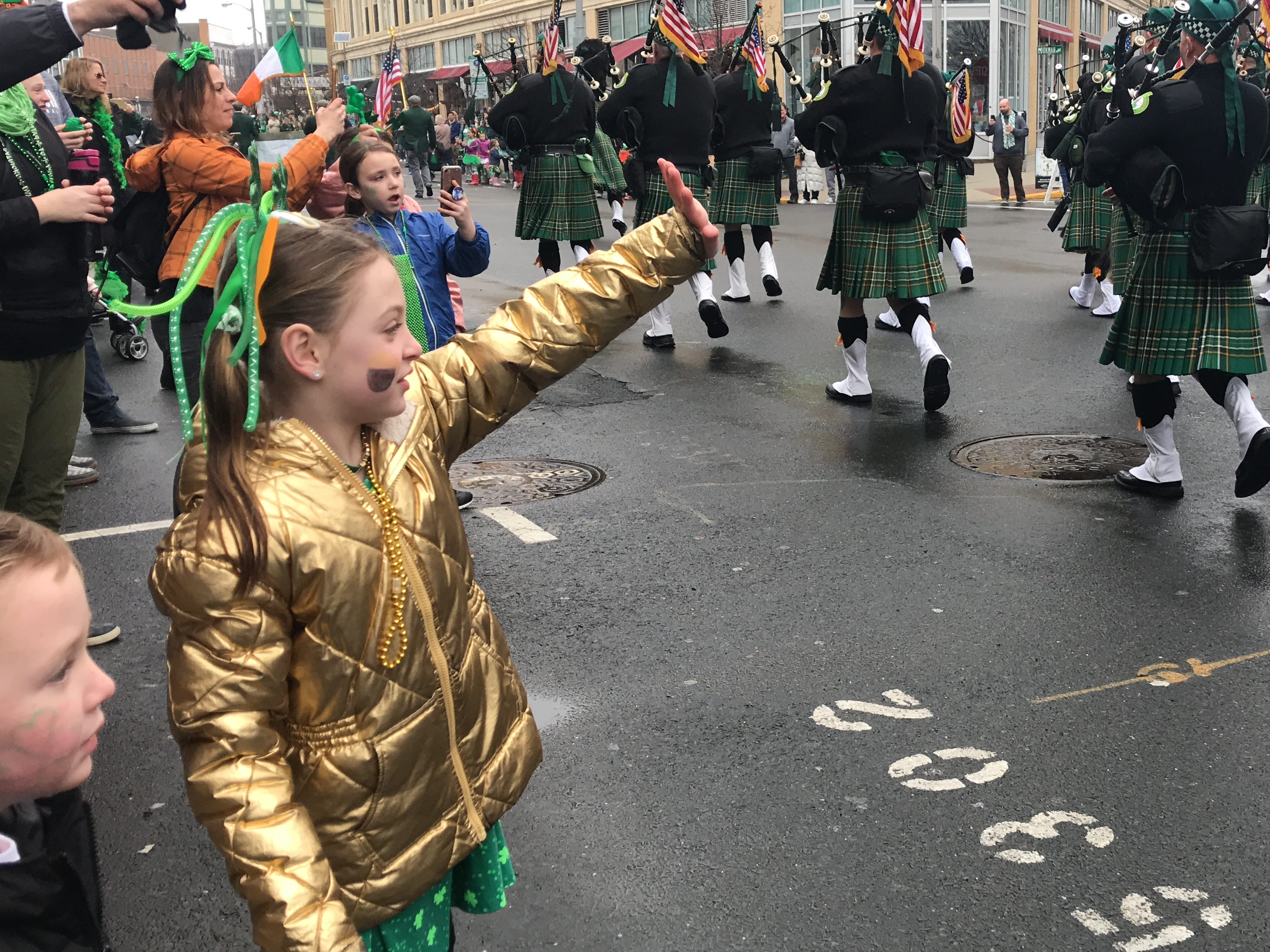 Ruby Delpriora, 6, of Howell, waves to marchers at the St. Patrick's Day Parade in Asbury Park on March 10, 2019.