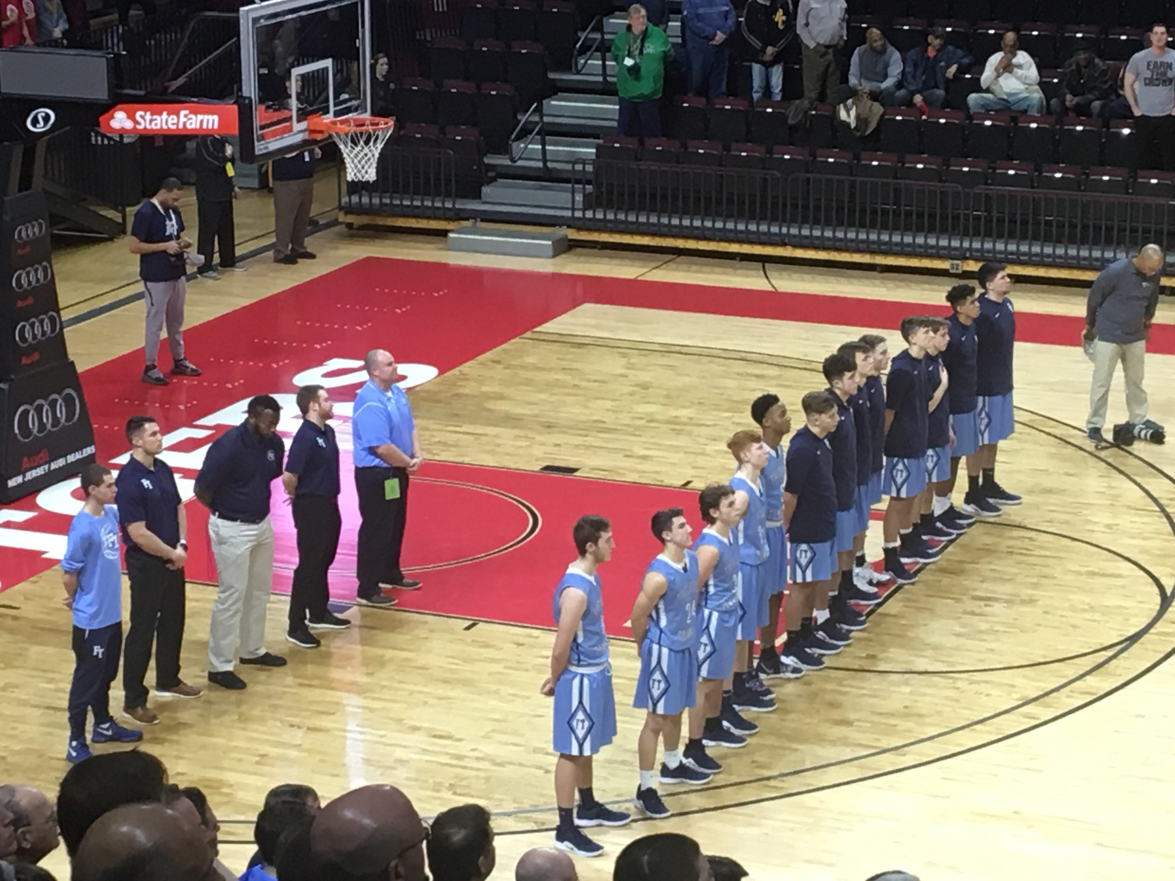 The Freehold Township boys basketball team and coaching staff observes the national anthem before the start of the Group IV State at Rutgers University on March 10, 2019