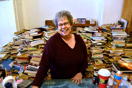A mound of books waiting to be sorted rises behind Martha Jarred, who stands Friday at the register in Haskell's Henderson Book Store. Martha and her husband Kenneth will close the used book store at the end of April.
