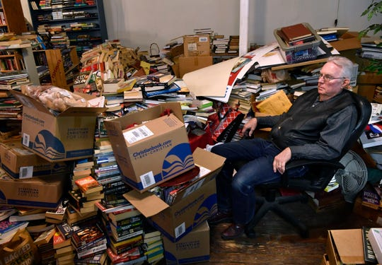 Kenneth Jarred sits in a chair March 8 among semi-organized piles of used books that his wife, Martha, and he had yet to catalog. Half-joking, he admitted at the time that closing the store by the end of April may be optimistic.