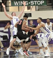 ACU's Hayden Farquhar, left, tries to draw  charge from Incarnate Word's Charles Brown (13) as Jaren Franklin defends. ACU beat the Cardinals 81-51 in the regular-season finale Saturday, March 9, 2019, at Moody Coliseum.