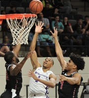 ACU's Jaren Lewis, center, shoots between two Incarnate Word defenders. The Wildcats won the game 81-51 on Saturday, March 9, 2019, at Moody Coliseum.