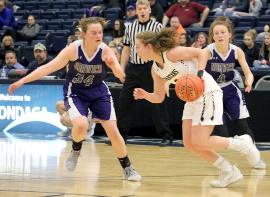 South Jefferson's Jackie Piddock maneuvers around Norwich's Nicole Jeffrey (34) and Sydney Coggins during the first half of Saturday's Class B state quarterfinal at Onondaga Community College. Piddock scored 17 points in the Spartans' 66-59 victory.