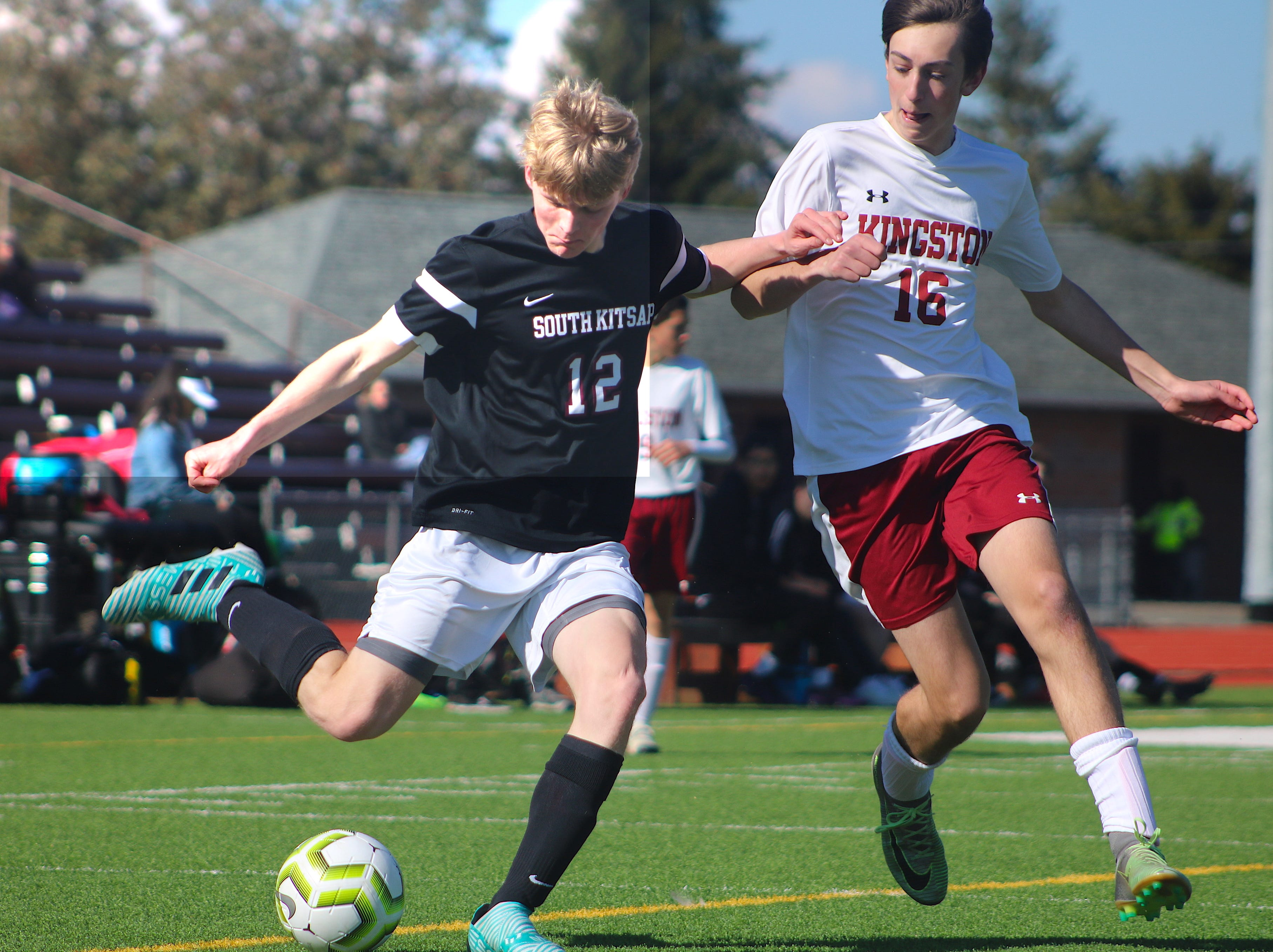 South Kitsap's Logan Anchick (left) prepares to cross the ball while Kingston's Eric Steele defends during Saturday's boys soccer game in Port Orchard.
