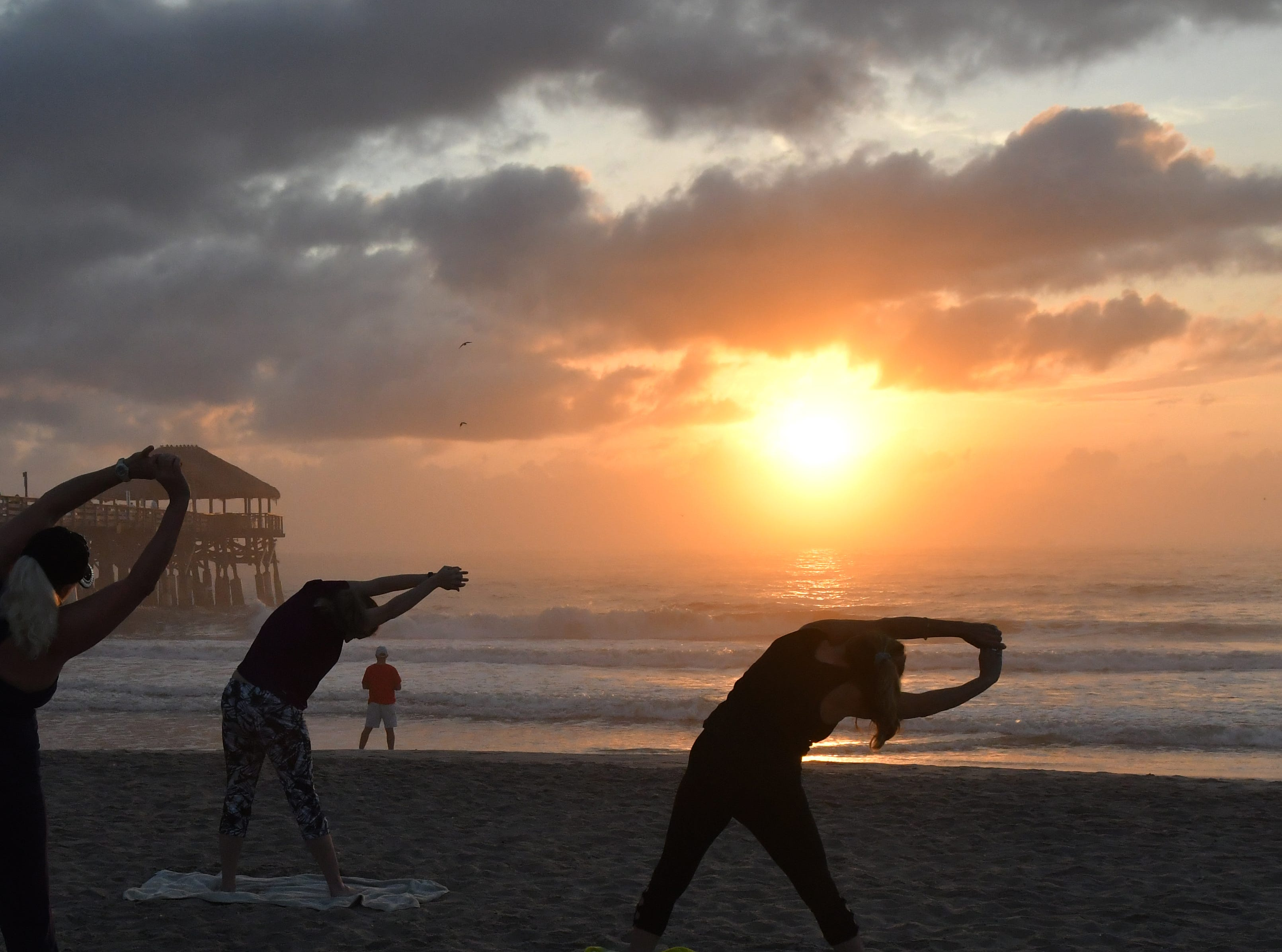 Sunrise Celebration Stretch at sunrise next to the Westgate Cocoa Beach Pier on the first day of Daylight Savings. This Yoga group, coordinated by Robin Taylor, meets at other locations as well. Left to right is Marissa Shebuski, Anne Lee, Robin Taylor, and Maria Shirley.
