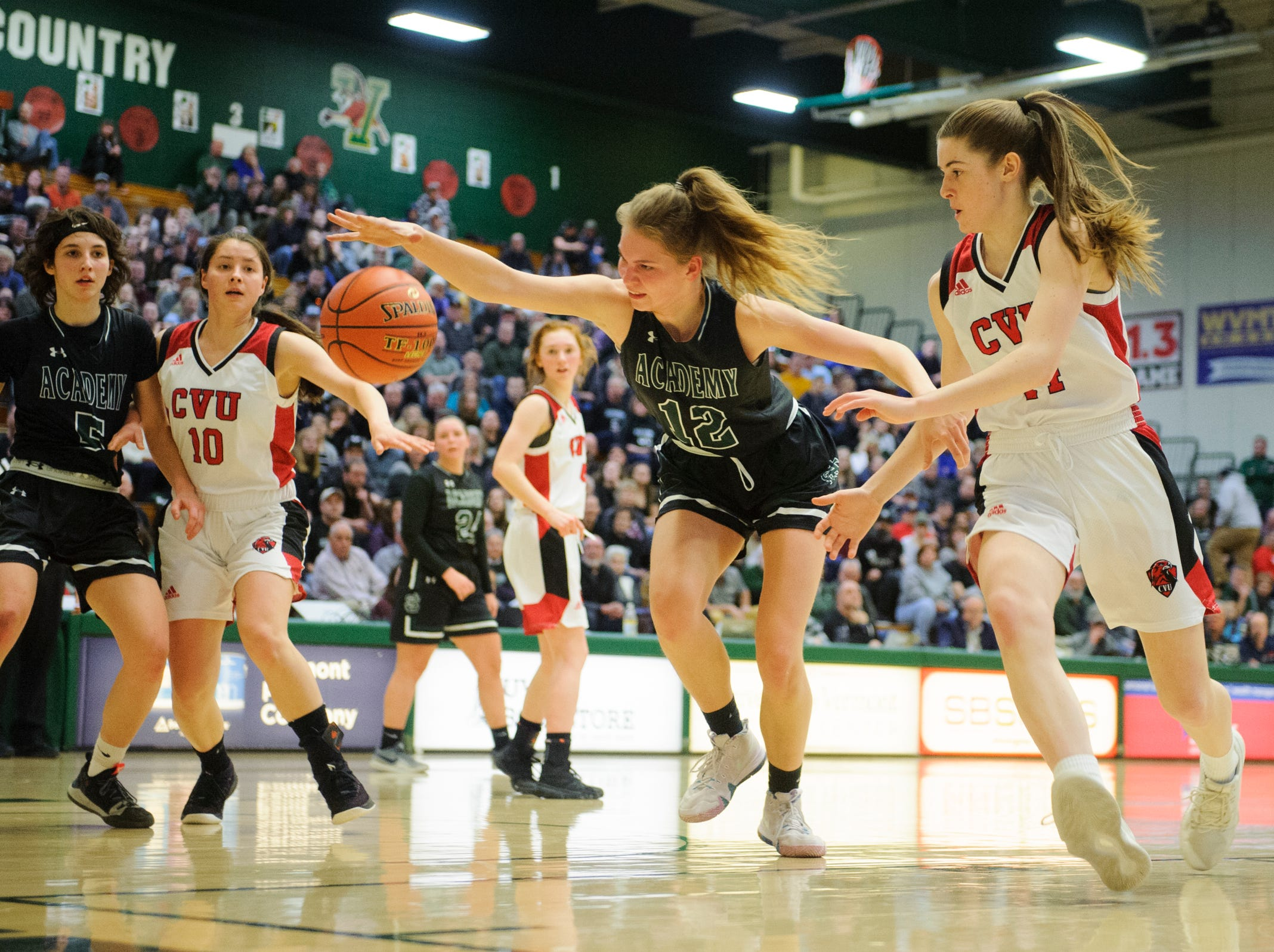 St. Johnsbury's Lara Rohkohl (12) battles for the loose ball with CVU's Julia Blanck (14) during the division I girls basketball championship basketball game between the St. Johnsbury Hilltoppers and the Champlain Valley Union Redhawks at Patrick Gym on Sunday afternoon March 10, 2019 in Burlington, Vermont.