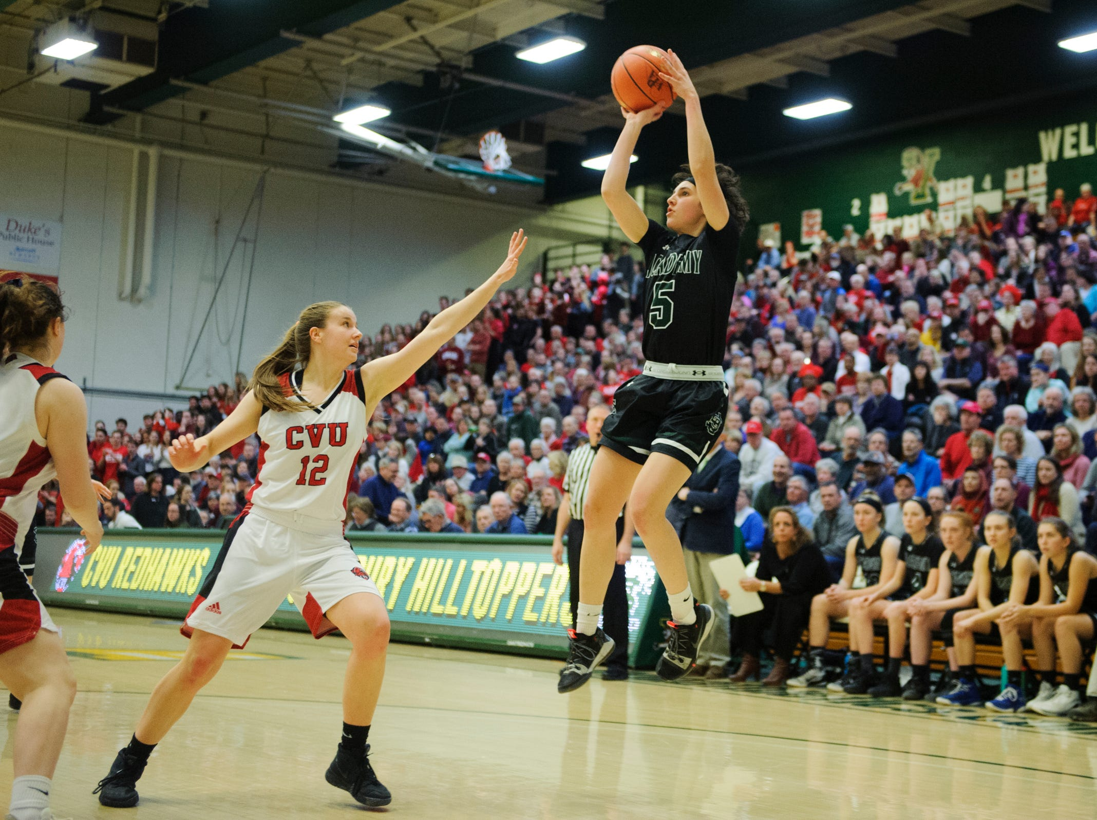 St. Johnsbury's Sadie Stetson (5) shoots the ball over CVU's Harper Mead (12) during the division I girls basketball championship basketball game between the St. Johnsbury Hilltoppers and the Champlain Valley Union Redhawks at Patrick Gym on Sunday afternoon March 10, 2019 in Burlington, Vermont.