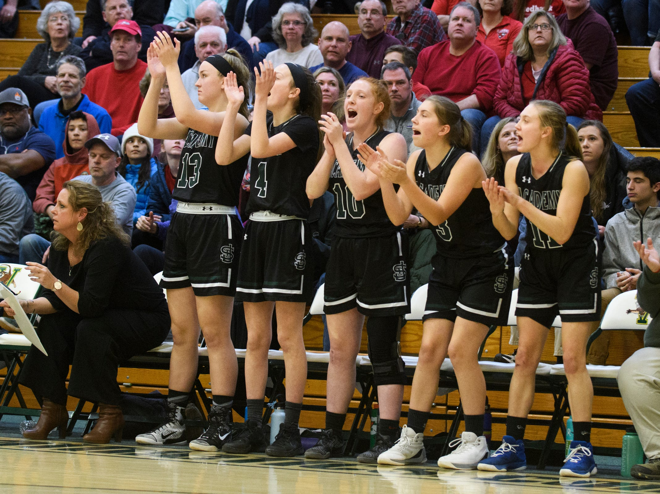 The St. Johnsbury bench cheers for the team during the division I girls basketball championship basketball game between the St. Johnsbury Hilltoppers and the Champlain Valley Union Redhawks at Patrick Gym on Sunday afternoon March 10, 2019 in Burlington, Vermont.