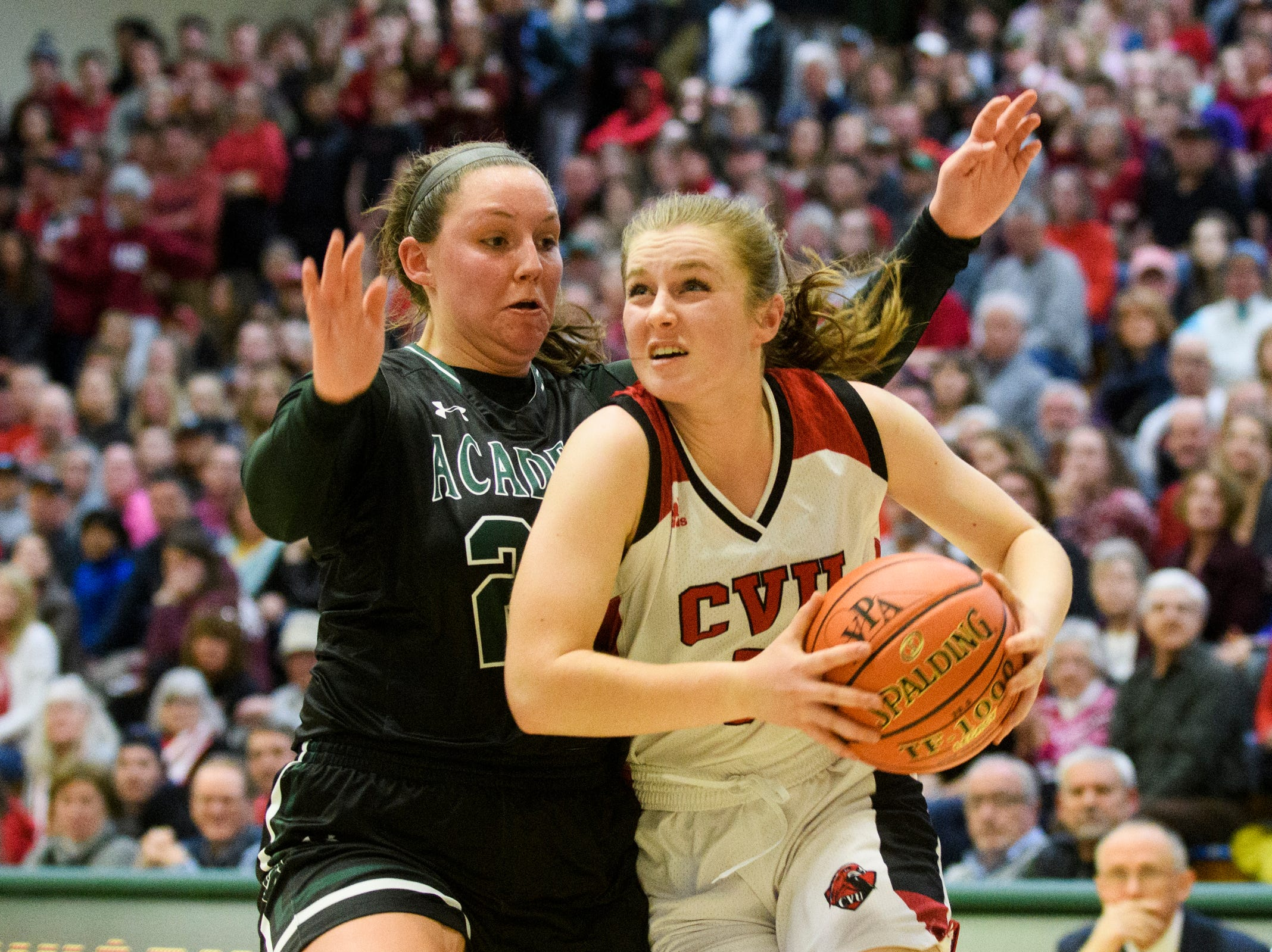 CVU's Mary Askew (5) drives to the hoop past St. Johnsbury's Josie Choiniere (24) during the division I girls basketball championship basketball game between the St. Johnsbury Hilltoppers and the Champlain Valley Union Redhawks at Patrick Gym on Sunday afternoon March 10, 2019 in Burlington, Vermont.