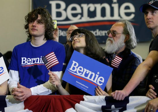 People listen as 2020 Democratic presidential candidate Sen. Bernie Sanders, not shown, addresses a rally during a campaign stop, Sunday, March 10, 2019, in Concord, N.H.