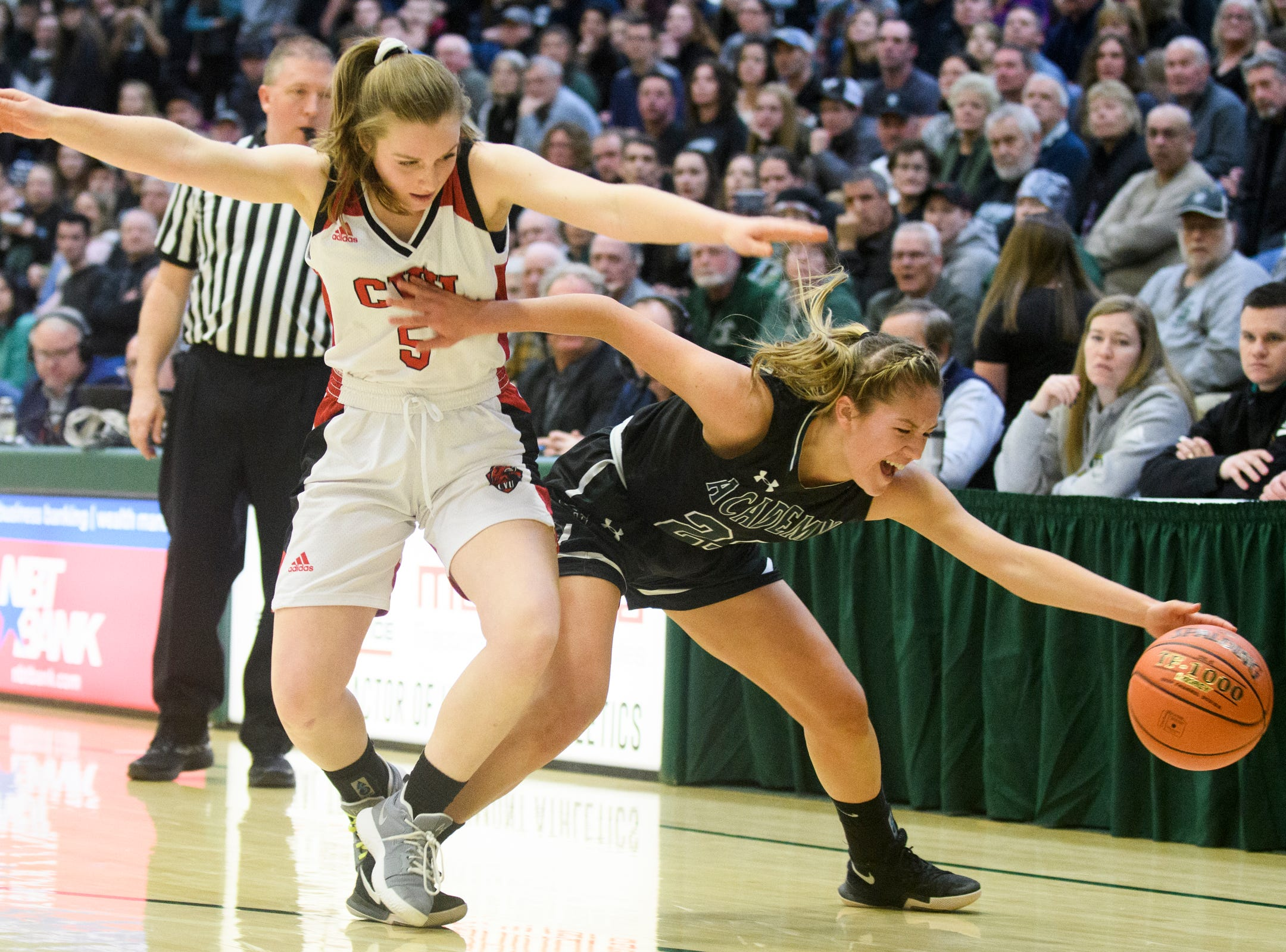St. Johnsbury's Neva Bostic (23) battles for the loose ball with CVU's Mary Askew (5) during the division I girls basketball championship basketball game between the St. Johnsbury Hilltoppers and the Champlain Valley Union Redhawks at Patrick Gym on Sunday afternoon March 10, 2019 in Burlington, Vermont.