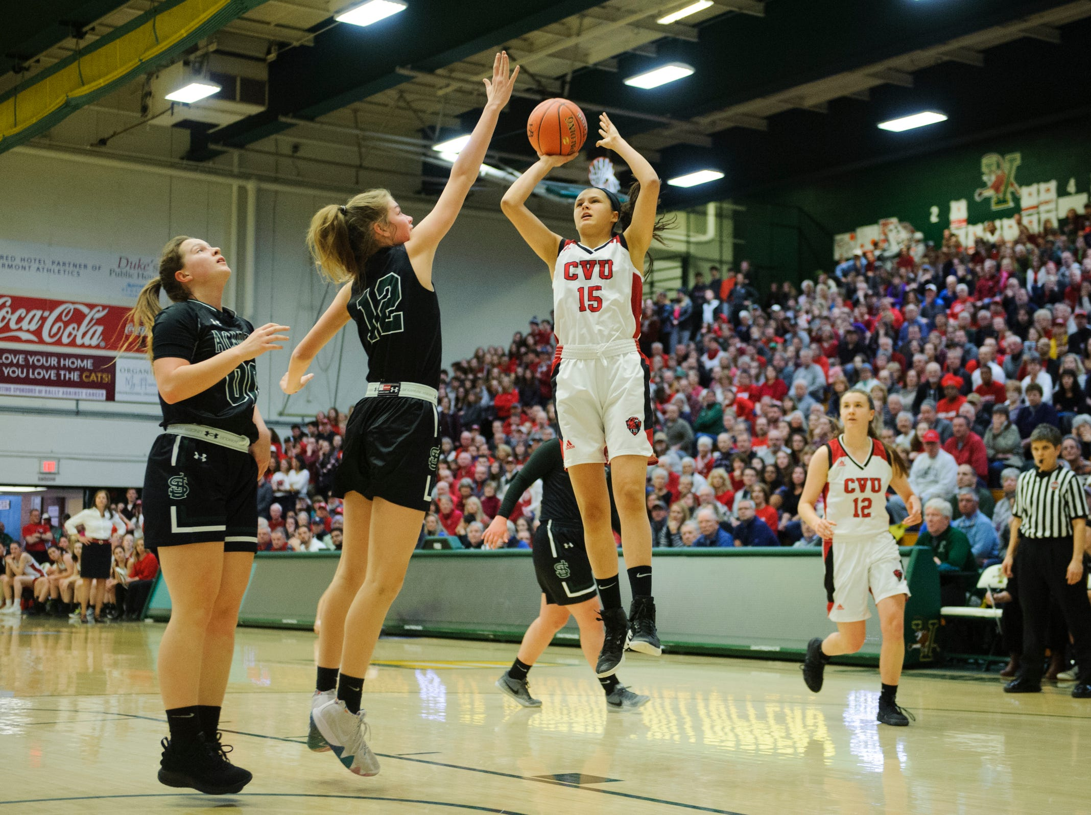 CVU's Bray Hunter (15) shoots the ball over St. Johnsbury's Lara Rohkohl (12) during the division I girls basketball championship basketball game between the St. Johnsbury Hilltoppers and the Champlain Valley Union Redhawks at Patrick Gym on Sunday afternoon March 10, 2019 in Burlington, Vermont.