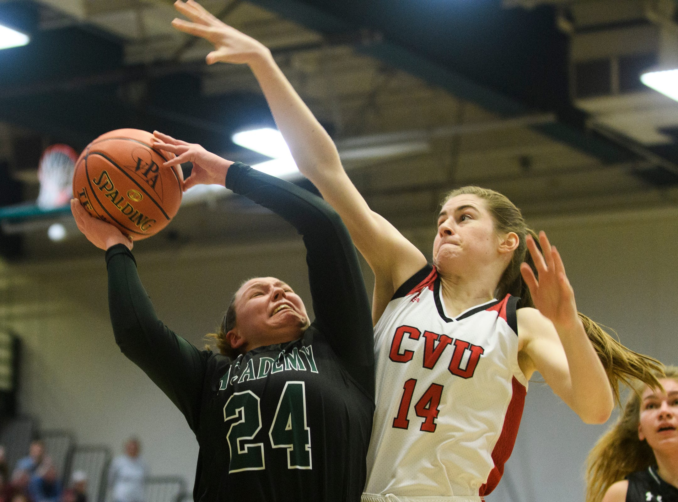 St. Johnsbury's Josie Choiniere (24) leaps for a lay up over CVU's Julia Blanck (14) during the division I girls basketball championship basketball game between the St. Johnsbury Hilltoppers and the Champlain Valley Union Redhawks at Patrick Gym on Sunday afternoon March 10, 2019 in Burlington, Vermont.