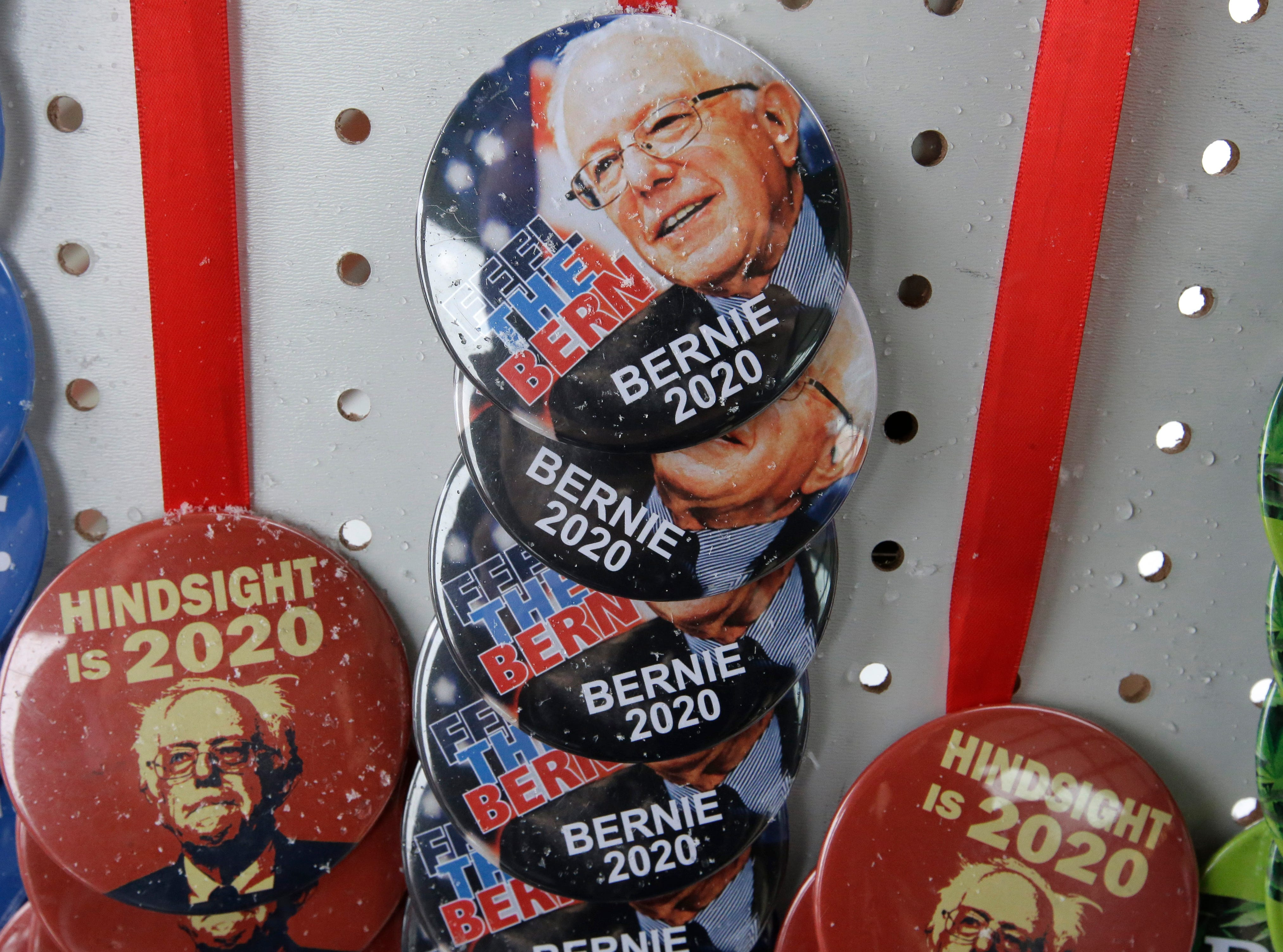 Buttons featuring the likeness of Sen. Bernie Sanders are dusted with snow in a vendor's stall outside the location of a scheduled campaign stop for the 2020 Democratic presidential candidate, Sunday, March 10, 2019, in Concord, N.H.