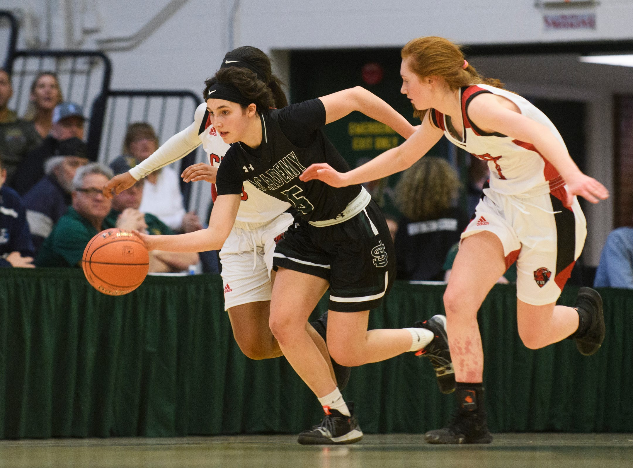 St. Johnsbury's Sadie Stetson (5) dribbles the ball down the court past CVU's Catherine Gilwee (4) and Mekkena Boyd (3) during the division I girls basketball championship basketball game between the St. Johnsbury Hilltoppers and the Champlain Valley Union Redhawks at Patrick Gym on Sunday afternoon March 10, 2019 in Burlington, Vermont.
