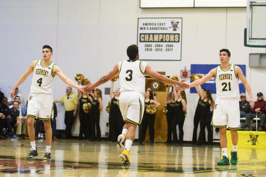 Vermont guard Robin Duncan (4) and Vermont guard Everett Duncan (21) high five Vermont forward Anthony Lamb (3) during the America East quarterfinal basketball game between the Maine Black Bears and the Vermont Catamounts at Patrick Gym on Saturday night March 9, 2019 in Burlington, Vermont.