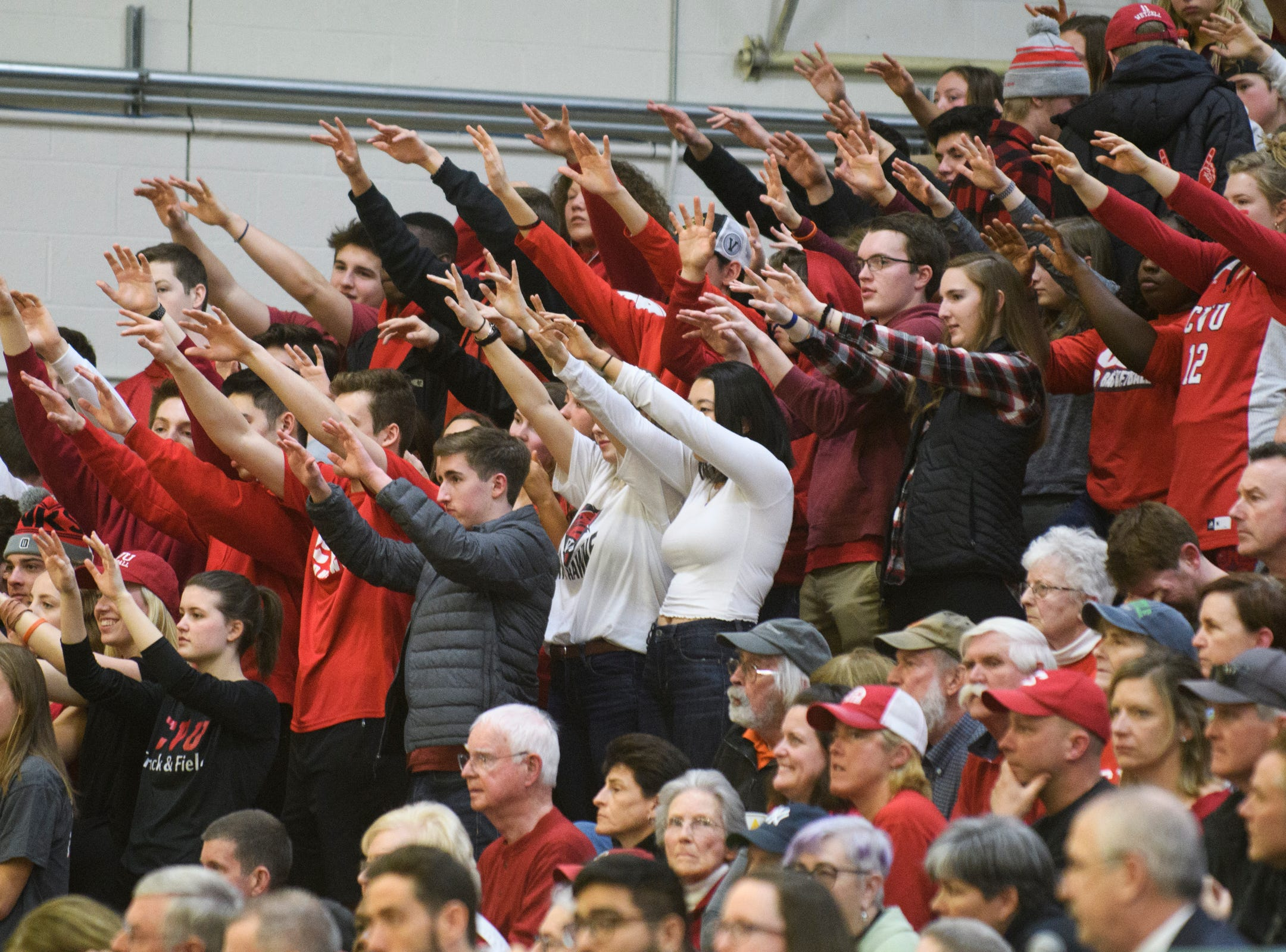 The CVU fans raise their hands during a free throw in the division I girls basketball championship basketball game between the St. Johnsbury Hilltoppers and the Champlain Valley Union Redhawks at Patrick Gym on Sunday afternoon March 10, 2019 in Burlington, Vermont.