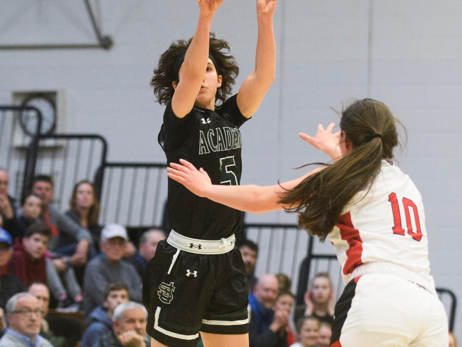St. Johnsbury's Sadie Stetson (5) shoots the ball over CVU's Quinn Boardman (10) during the division I girls basketball championship basketball game between the St. Johnsbury Hilltoppers and the Champlain Valley Union Redhawks at Patrick Gym on Sunday afternoon March 10, 2019 in Burlington, Vermont.