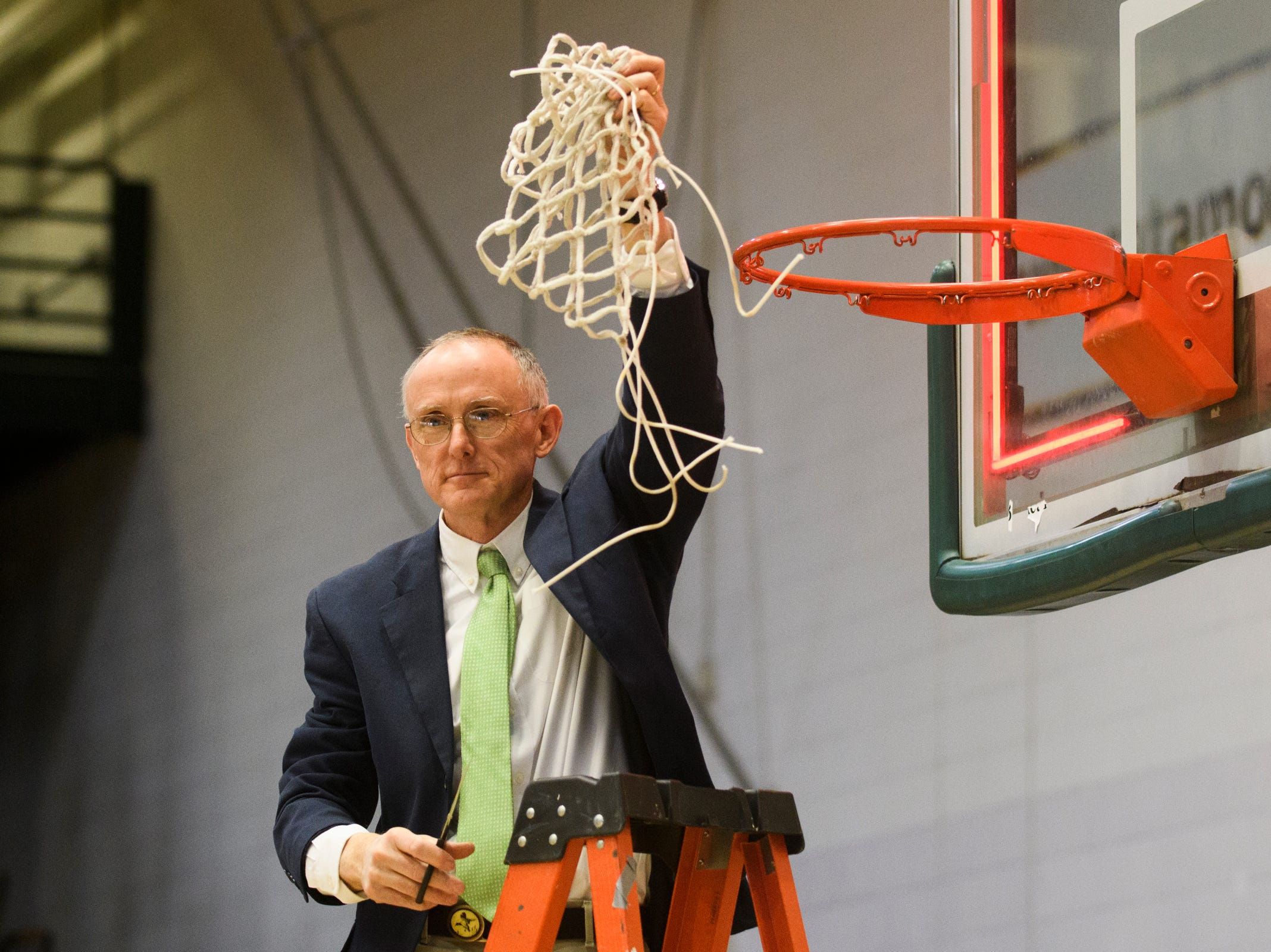 St. Johnsbury head coachJack Driscoll holds up the net for the fans during the division I girls basketball championship basketball game between the St. Johnsbury Hilltoppers and the Champlain Valley Union Redhawks at Patrick Gym on Sunday afternoon March 10, 2019 in Burlington, Vermont.