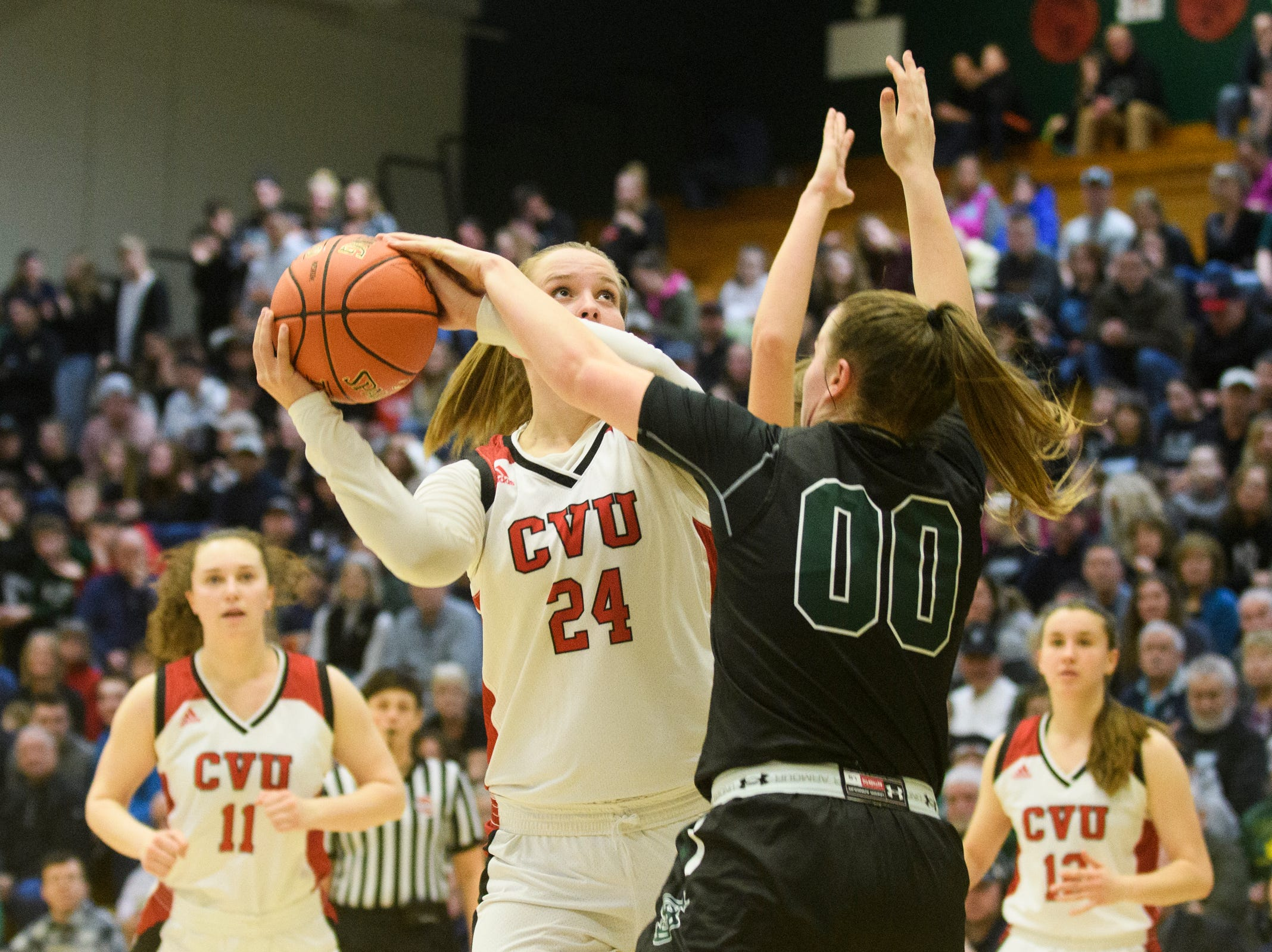 St. Johnsbury's Saleena Porter (00) fouls CVU's Kaylee Beyor (24) as she drives to the hoop during the division I girls basketball championship basketball game between the St. Johnsbury Hilltoppers and the Champlain Valley Union Redhawks at Patrick Gym on Sunday afternoon March 10, 2019 in Burlington, Vermont.