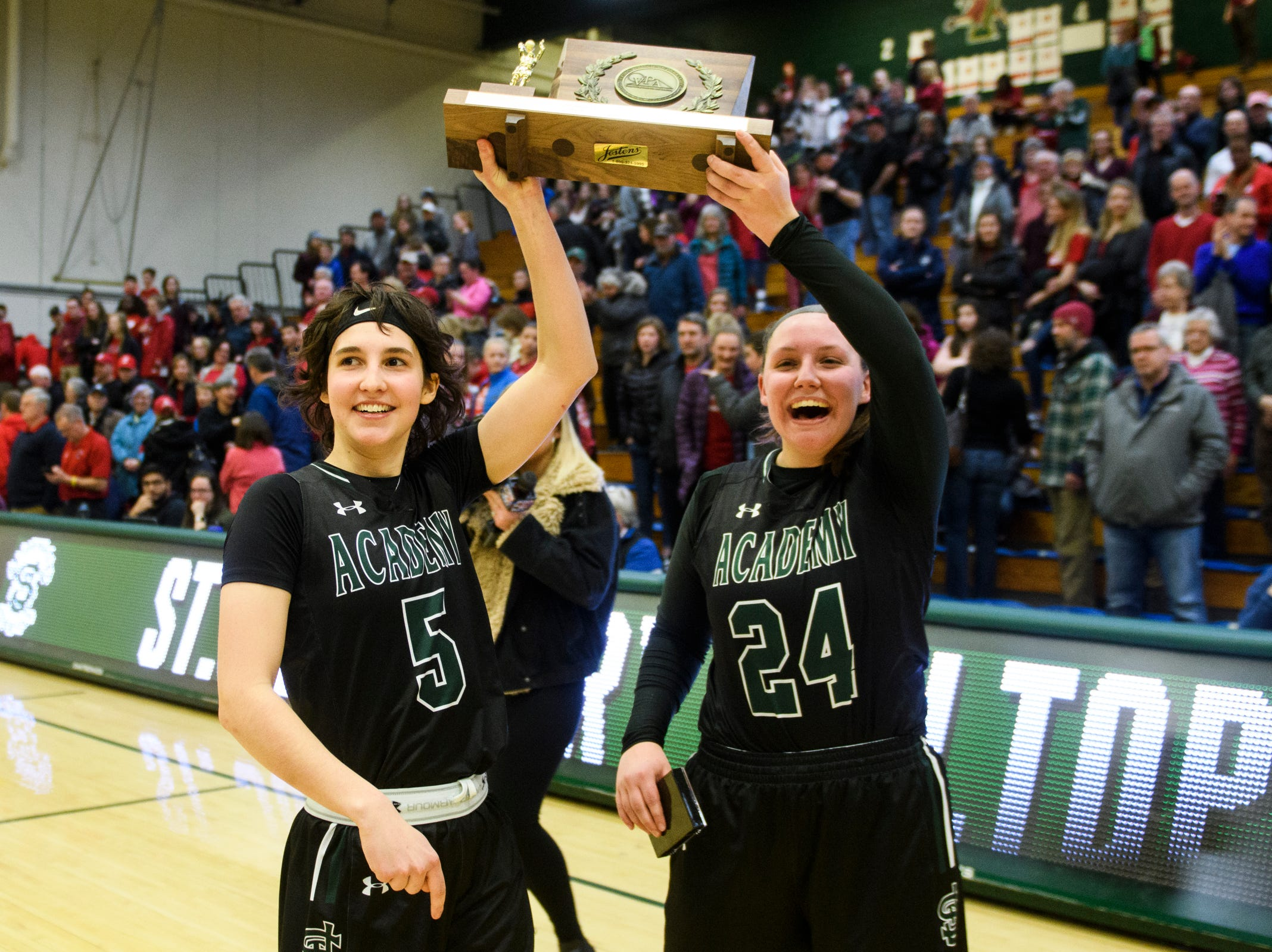 St. Johnsbury captains Sadie Stetson (5) and Josie Choiniere (24) hold up the championship trophy during the division I girls basketball championship basketball game between the St. Johnsbury Hilltoppers and the Champlain Valley Union Redhawks at Patrick Gym on Sunday afternoon March 10, 2019 in Burlington, Vermont.