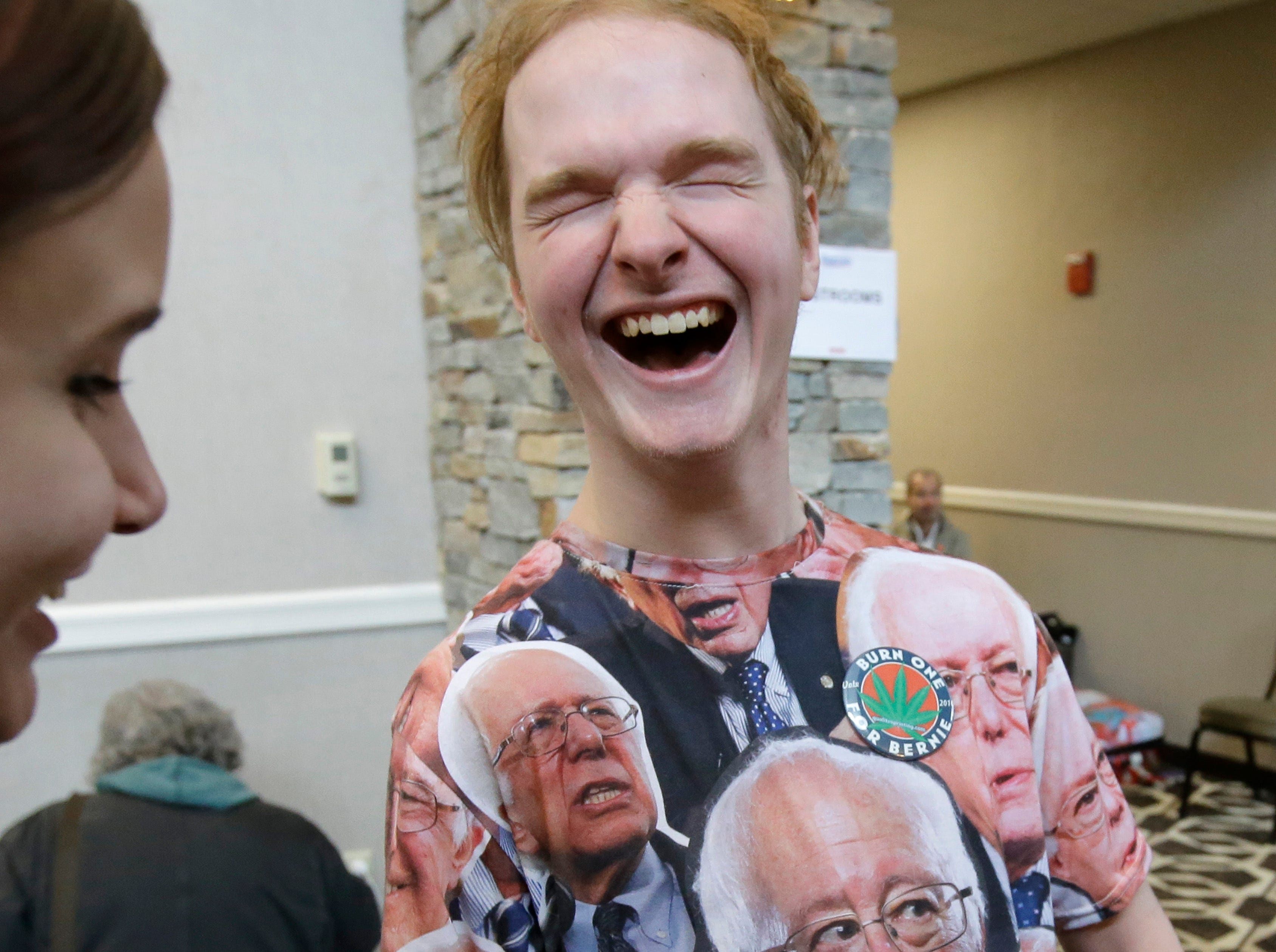 Douglas Frenette, of Amherst, N.H., center, wears a shirt featuring the likeness of 2020 Democratic presidential candidate Sen. Bernie Sanders, as Frenette is asked to sign a petition outside the location of a scheduled Sanders campaign event, Sunday, March 10, 2019, in Concord, N.H.