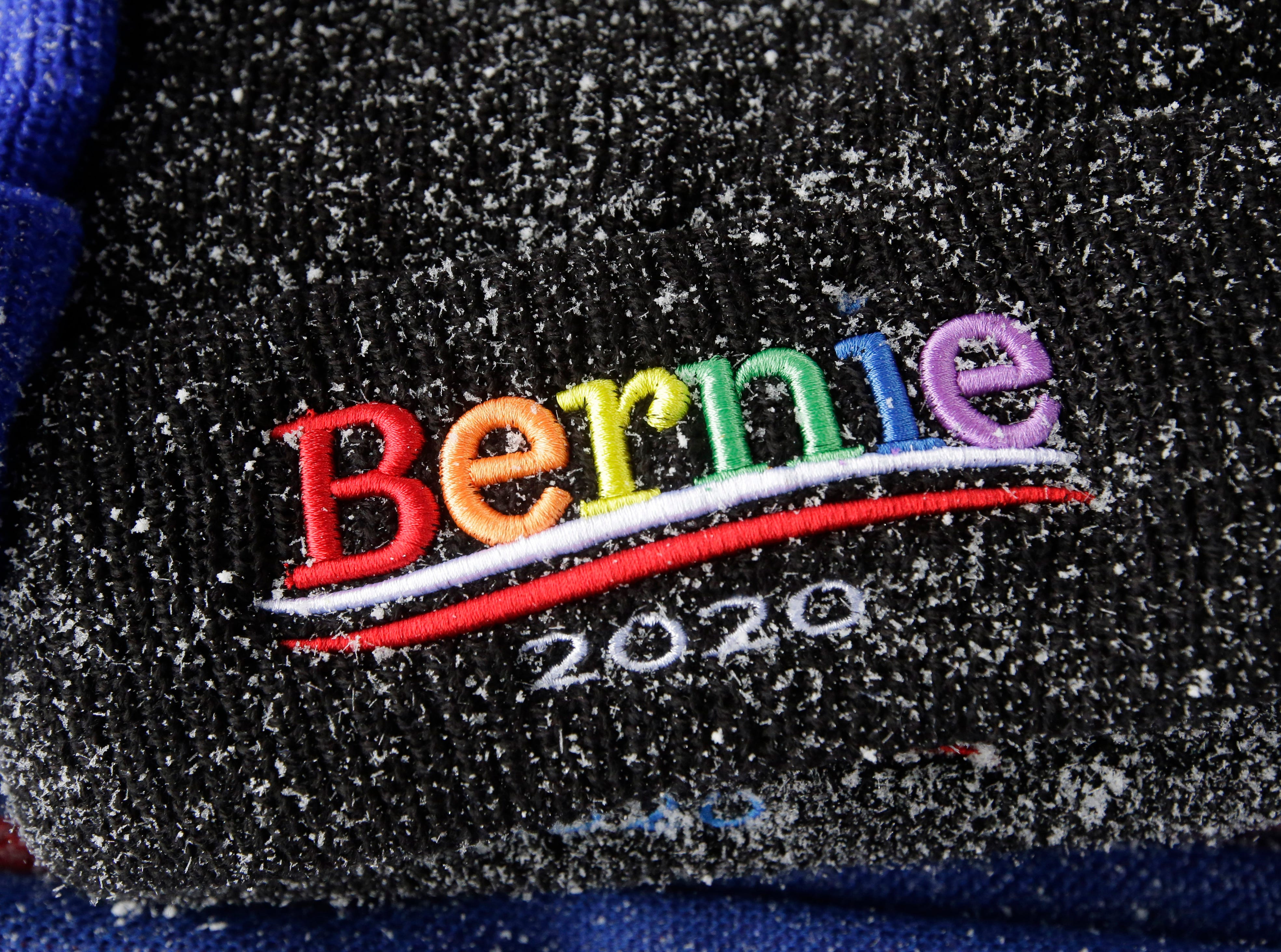 A hat featuring a campaign logo is dusted with snow in a vendor's stall outside the location of a scheduled campaign stop for 2020 Democratic presidential candidate Sen. Bernie Sanders, Sunday, March 10, 2019, in Concord, N.H.