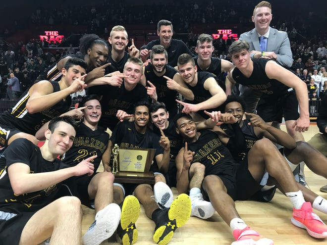 The Moorestown boys basketball team celebrates after winning its first state title in 60 years on Sunday. The Quakers defeated Ramapo 58-44 in the Group 3 state final at Rutgers.