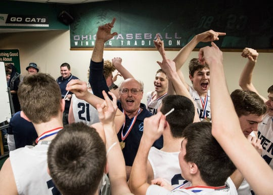 The Adena boys' basketball team celebrate inside their locker room after clenching a Division III district final at Ohio University's Convocation Center.