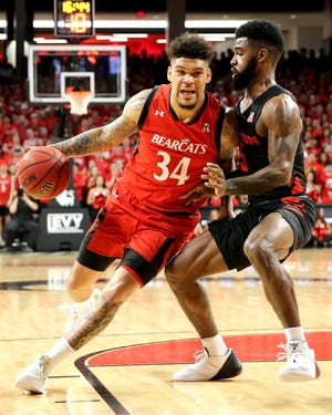 Cincinnati Bearcats guard Jarron Cumberland (34) drives to the basket as Houston Cougars guard Corey Davis Jr. (5) defends in the first half of an NCAA college basketball game, Sunday, March 10, 2019, at Fifth Third Arena in Cincinnati.