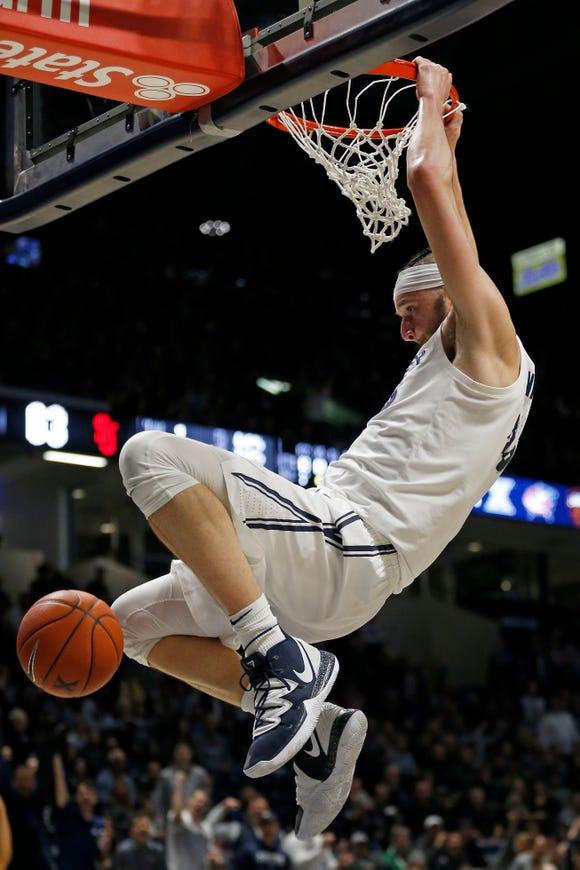 Xavier Musketeers forward Zach Hankins (35) hangs on the rim after a dunk in the second half of the NCAA Big East game between the Xavier Musketeers and the St. John's Red Storm at the Cintas Center in Cincinnati on Saturday, March 9, 2019. Xavier won its final game of the regular season, 81-68.