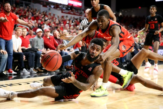 Houston Cougars guard Corey Davis Jr. (5) passes the ball as Cincinnati Bearcats guard Keith Williams (2) defends in the first half of an NCAA college basketball game, Sunday, March 10, 2019, at Fifth Third Arena in Cincinnati.