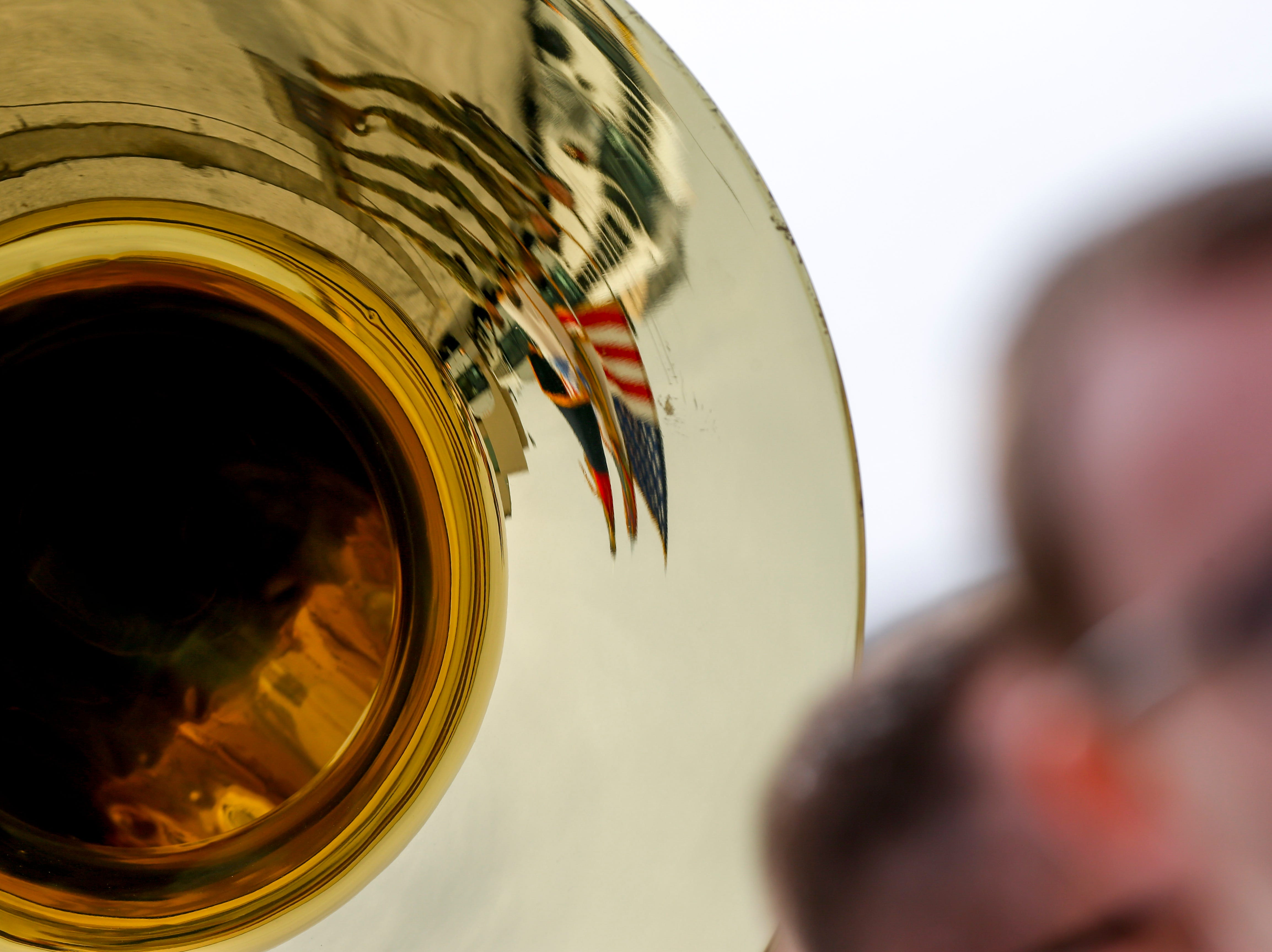 The American flag and 101st Airborne Division colors reflect on a sousaphone from the Army Band during the return of soldiers from the 101st Combat Aviation Brigade of 101st Airborne Division (Air Assault) at Campbell Army Air Field in Fort Campbell, KY., on Sunday, March 10, 2019.