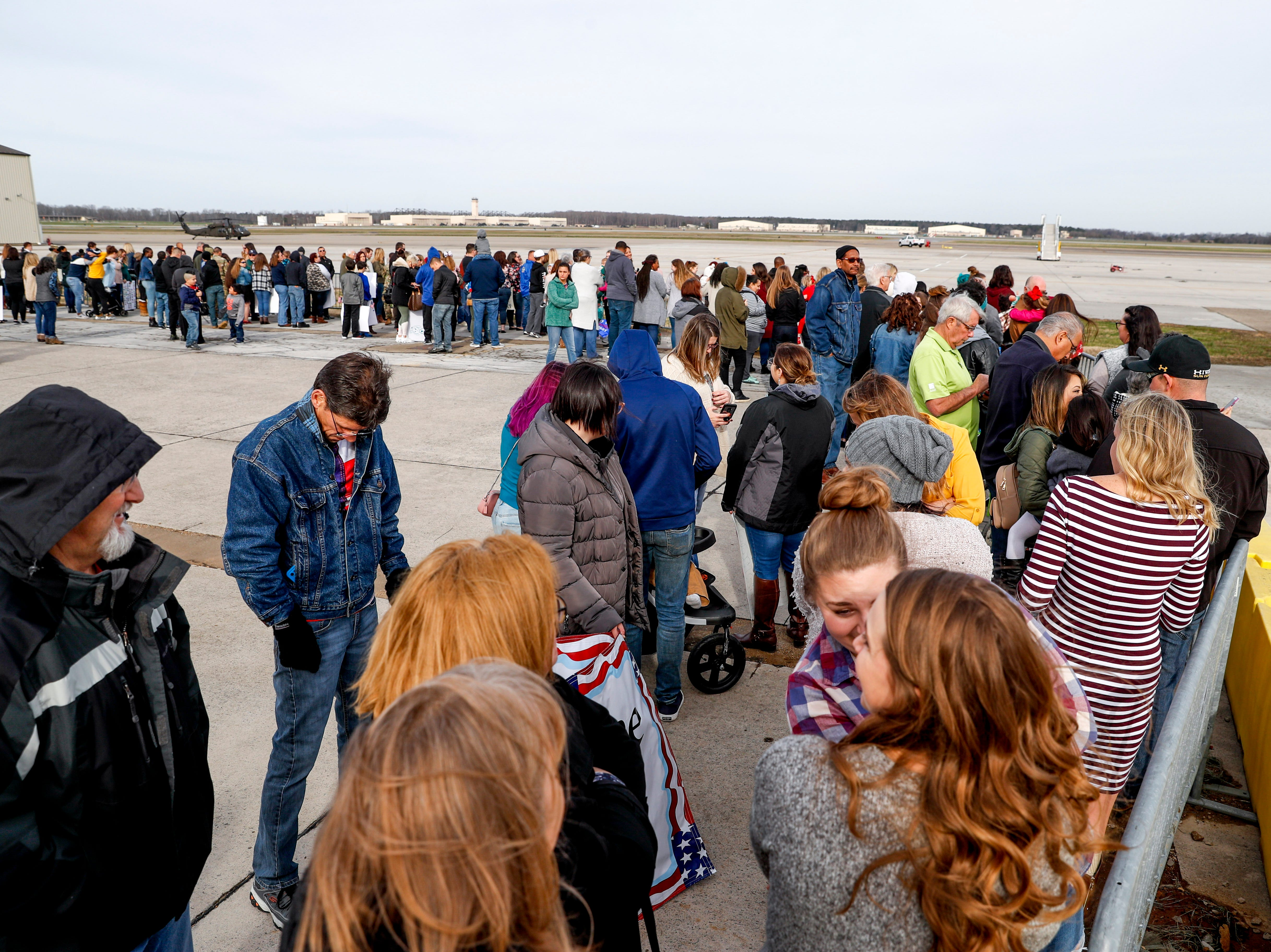 Family members line up against fencing waiting to see loved ones returning from deployment in Afghanistan during the return of soldiers from the 101st Combat Aviation Brigade of 101st Airborne Division (Air Assault) at Campbell Army Air Field in Fort Campbell, KY., on Sunday, March 10, 2019.