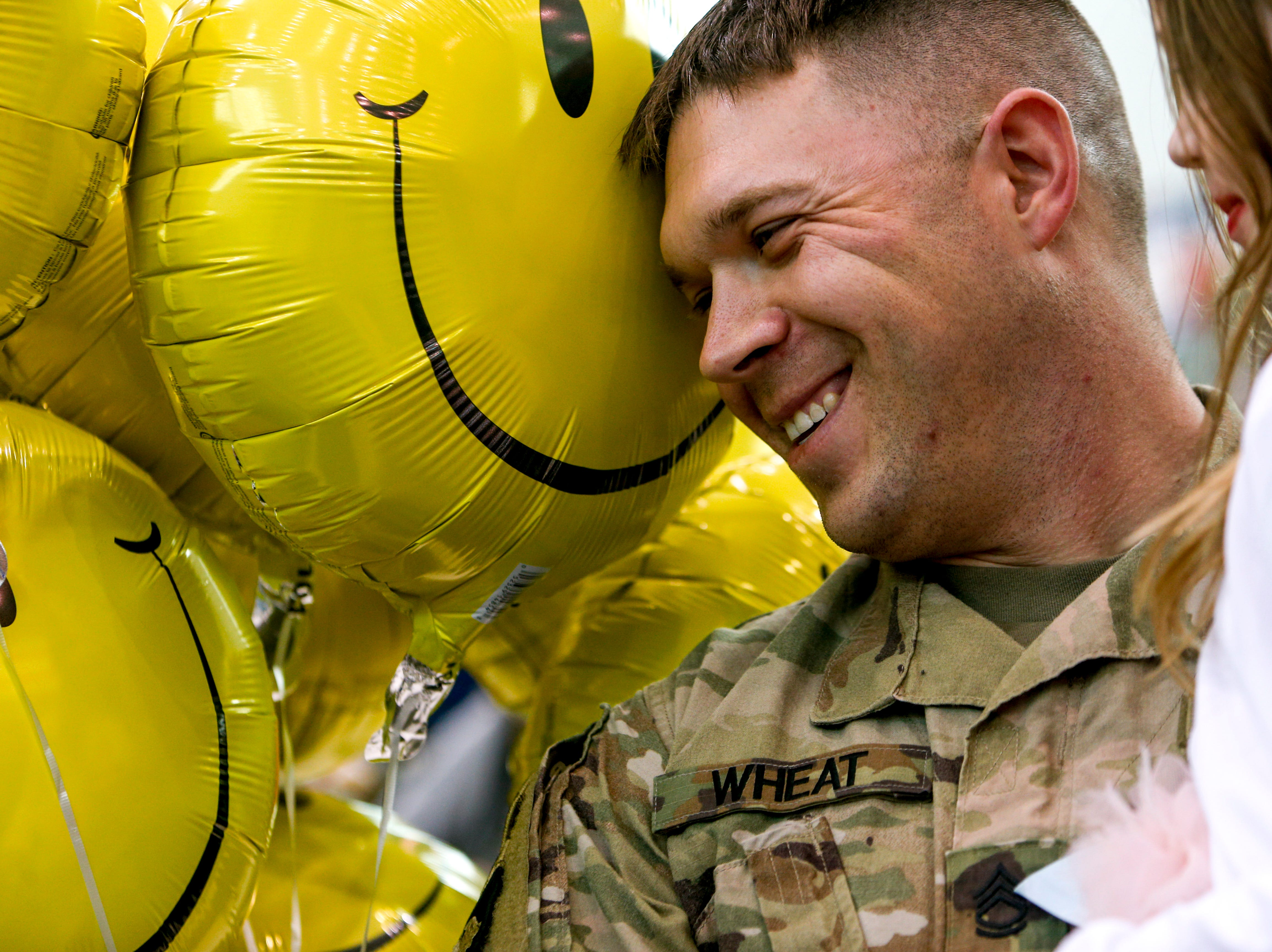 Sgt. Logan Wheat smiles at his family while holding up his daughter Annabelle Wheat, 7, upon seeing her for the first time after deployment during the return of soldiers from the 101st Combat Aviation Brigade of 101st Airborne Division (Air Assault) at Campbell Army Air Field in Fort Campbell, KY., on Sunday, March 10, 2019.