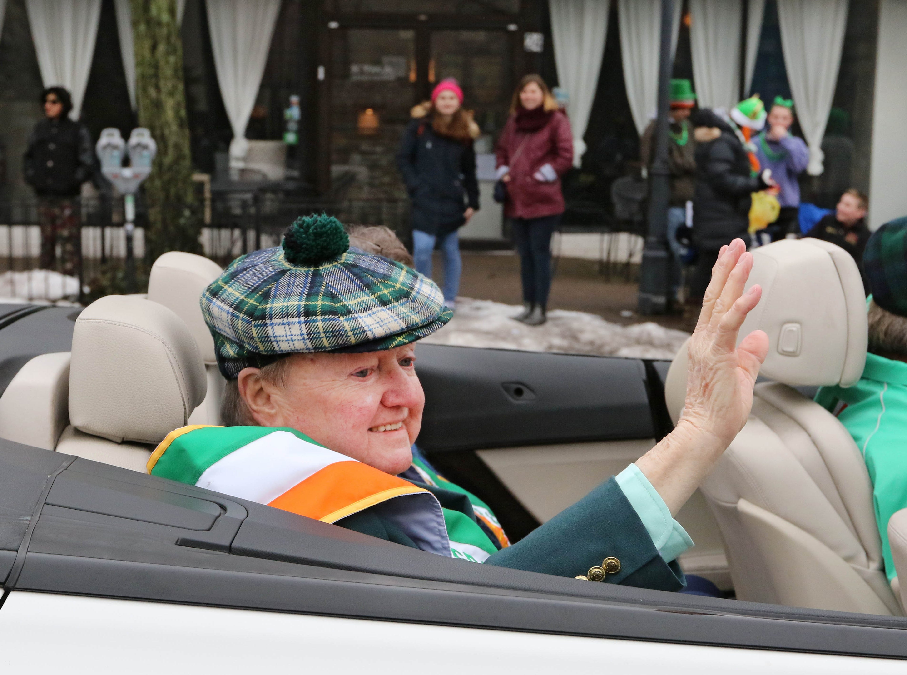 Grand Marshall Jim Walsh waves to the crowd during the 28th Somerville St. Patrick's Parade along Main Street on Sunday.
