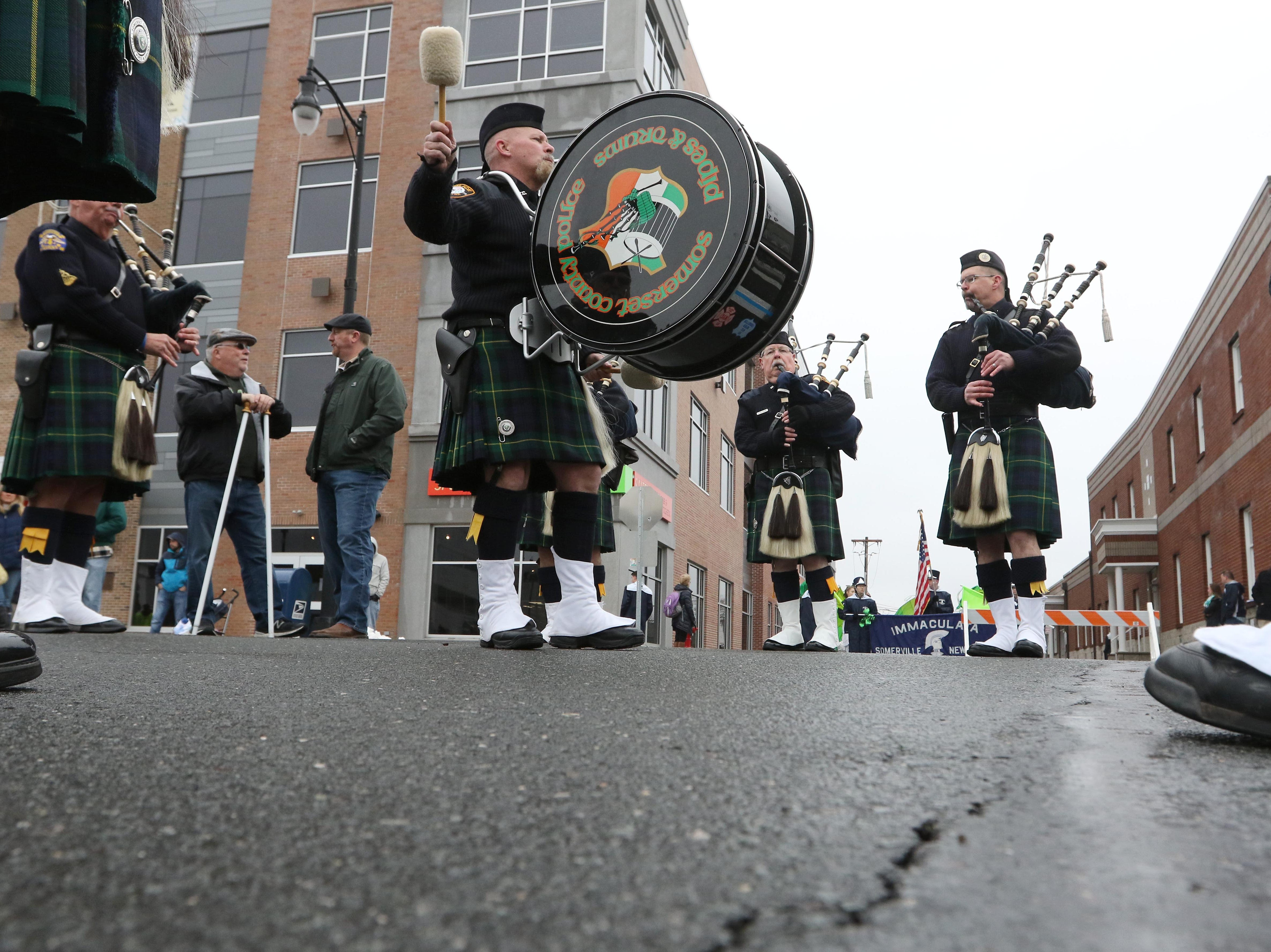 Base drum player Dennis MacMinn, warms up with the Somerset County Police Pipes and Drums before the start of the 28th Somerville St. Patrick's Parade along Main Street on Sunday.