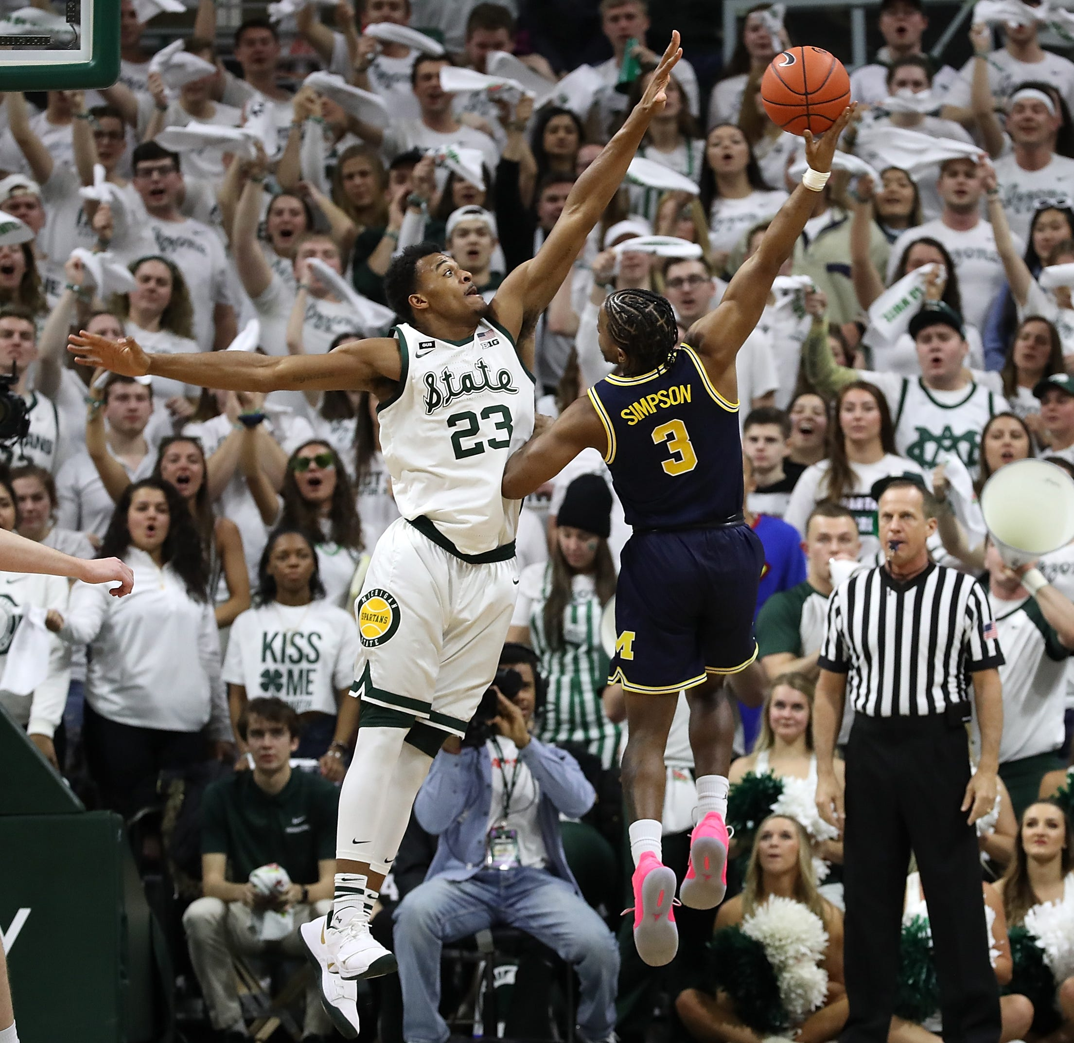 Michigan guard Zavier Simpson attempts a shot around Michigan State's Xavier Tillman during the first half at Breslin Center on March 9, 2019 in East Lansing.
