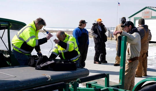 Fisherman James Gibelyou,  left, watches a rescue crew on a airboat prepare to go back on the ice to rescue stranded fishermen off Catawba Island State Park, Ohio in Lake Erie, on Saturday, March 9, 2019.