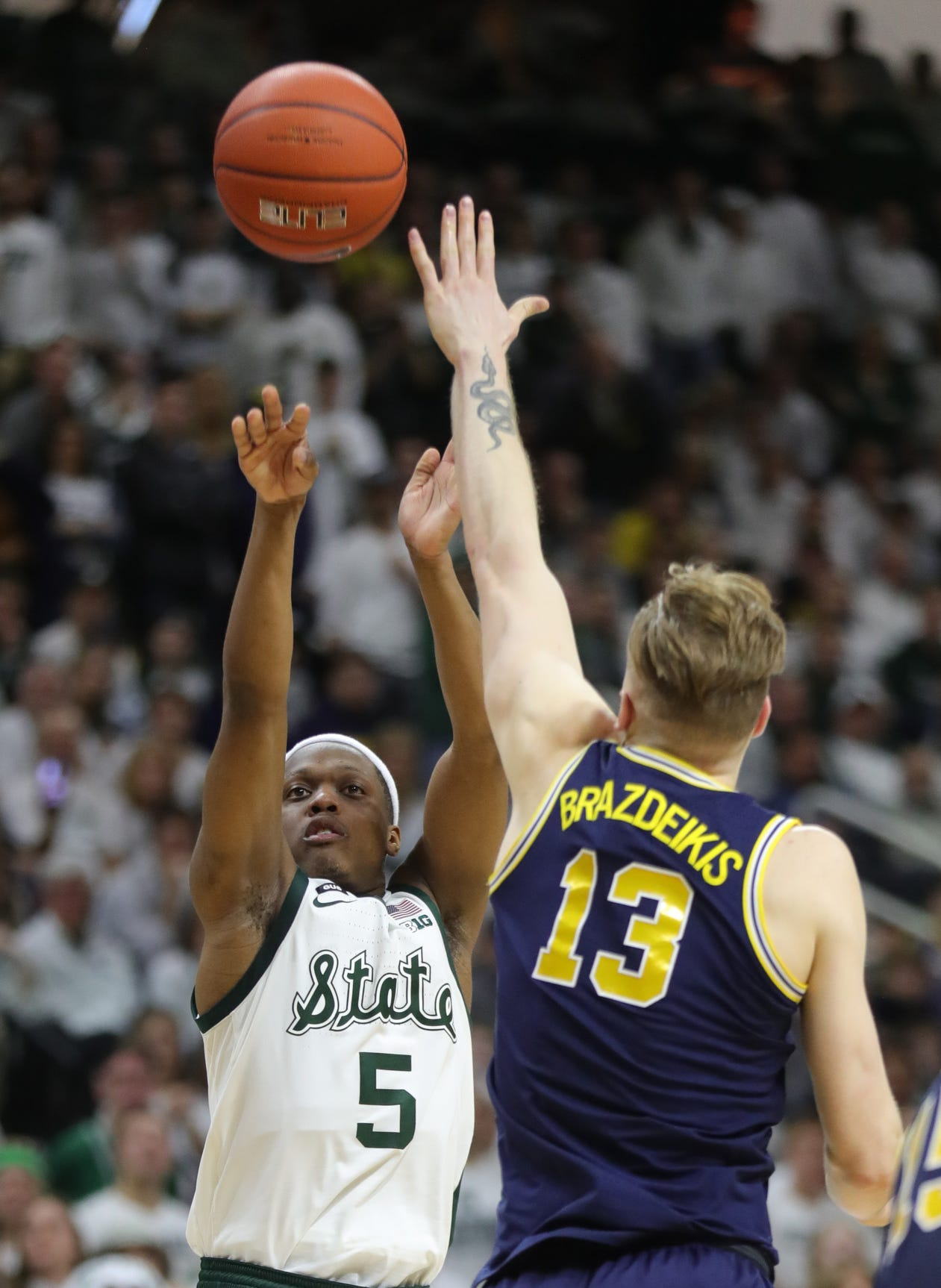 Michigan State guard Cassius Winston scores against Michigan forward Ignas Brazdeikis during the second half Saturday, March 9, 2019 at the Breslin Center in East Lansing.