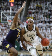 Michigan State guard Cassius Winston drives against Michigan guard Zavier Simpson on Saturday at Breslin Center in East Lansing. Winston scored 23 points as the Spartans won, 75-63, to claim a share of the Big Ten regular-season title.