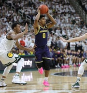 Michigan guard David DeJulius passes against Michigan State forward Xavier Tillman during first half action Saturday, March 9, 2019 at the Breslin Center in East Lansing, Mich.